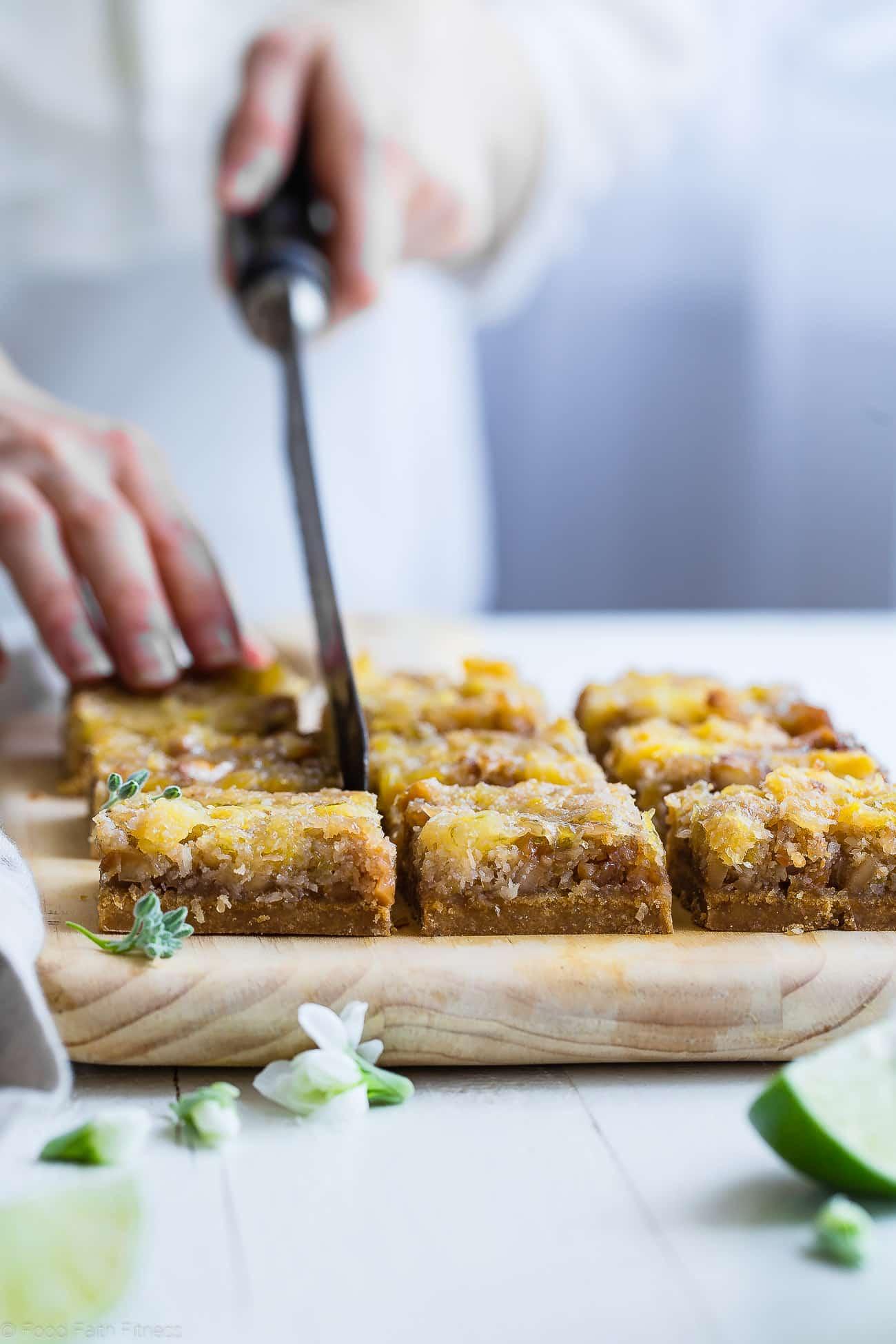 cutting tropical paleo magic cookie bars. Recipe on foodfaithfitness.com