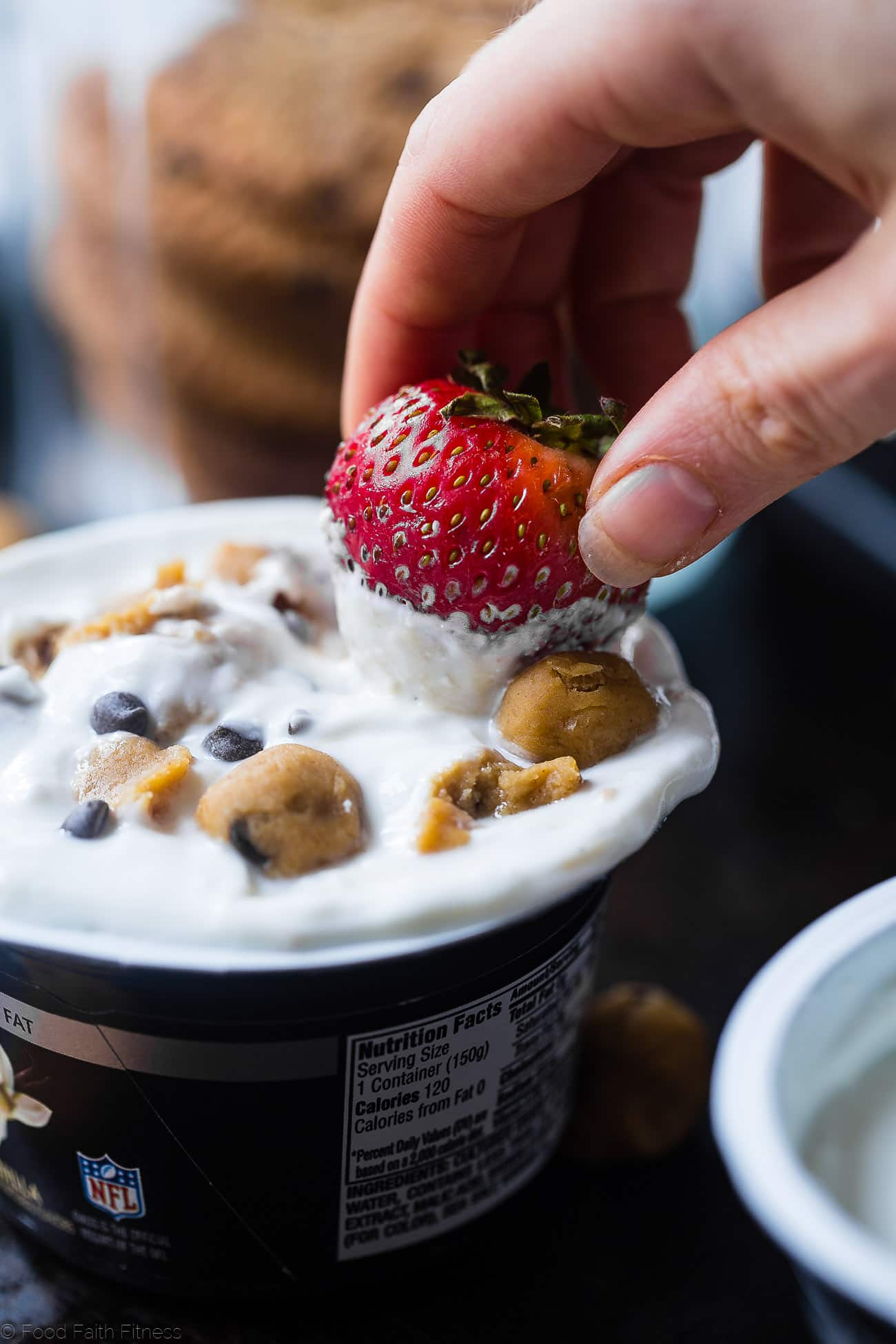 Dipping a strawberry into cookie dough dip. Recipe on Foodfaithfitness.com