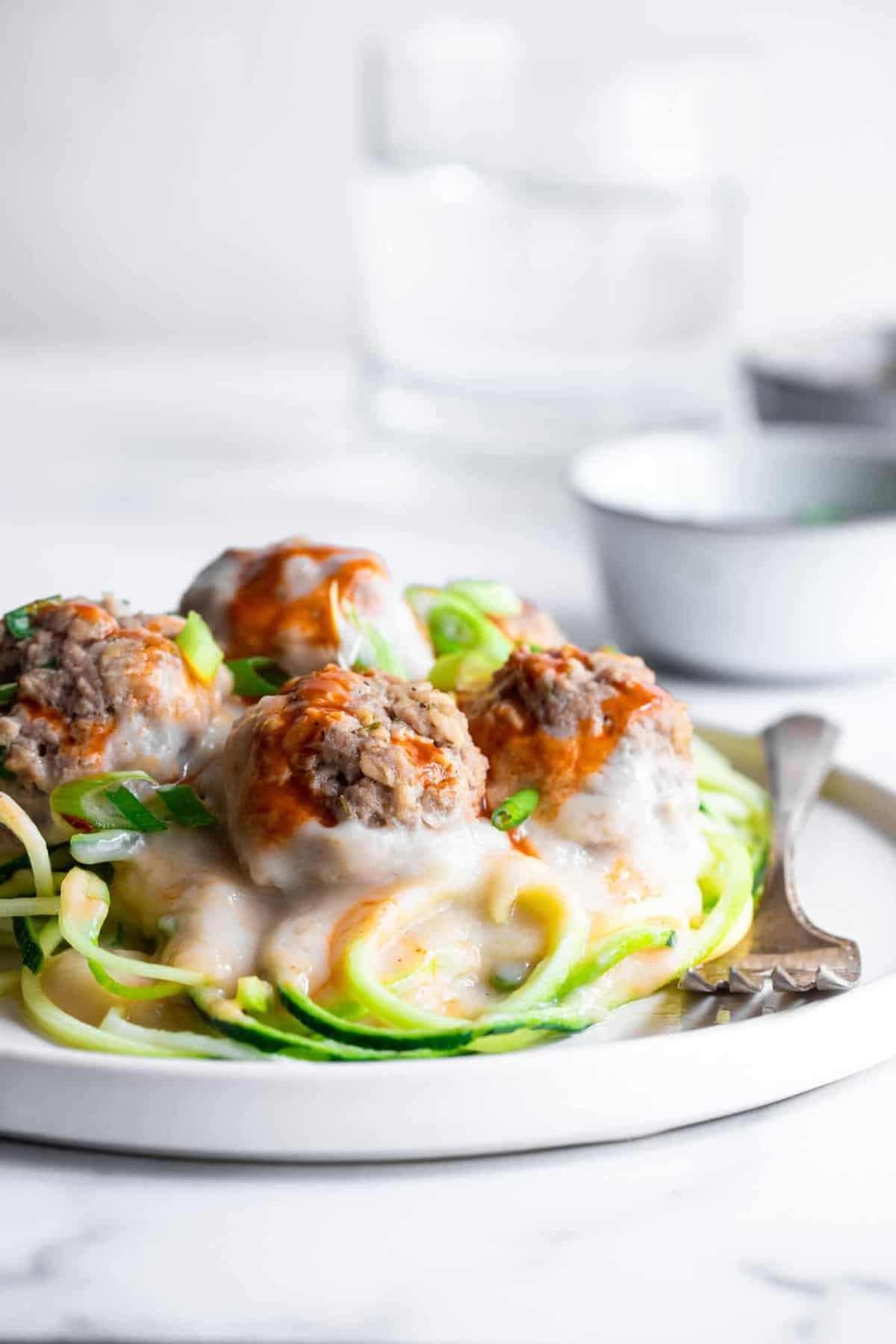 Low carb buffalo chicken meatballs on a pile of zucchini noodles