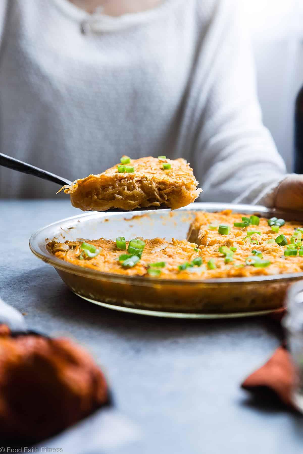 a person serving a slice of paleo buffalo chicken spaghetti squash casserole