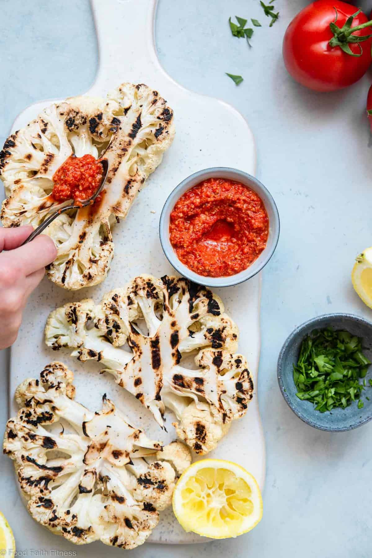 A hand spreading sauce on cauliflower steak on the grill