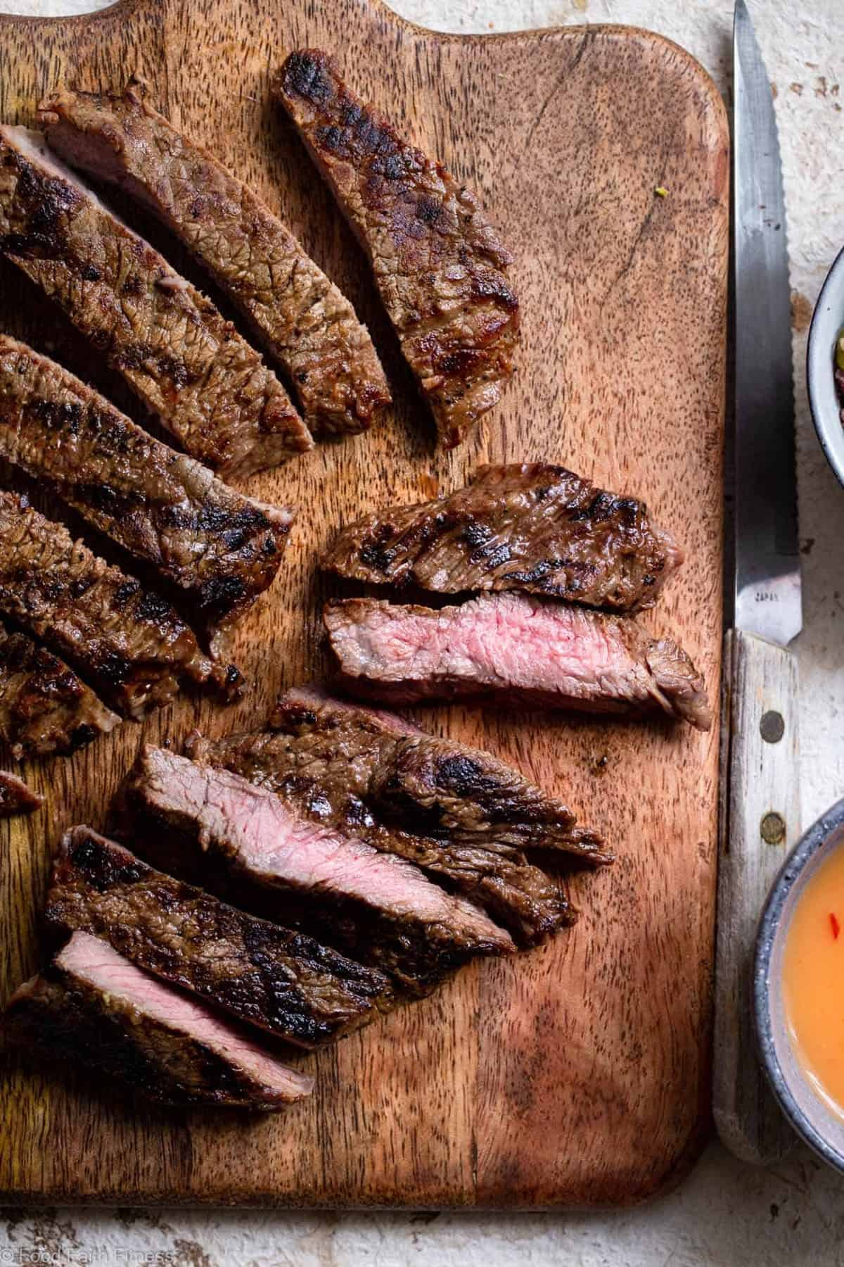 Sliced steak on a cutting board for Spicy Thai beef salad