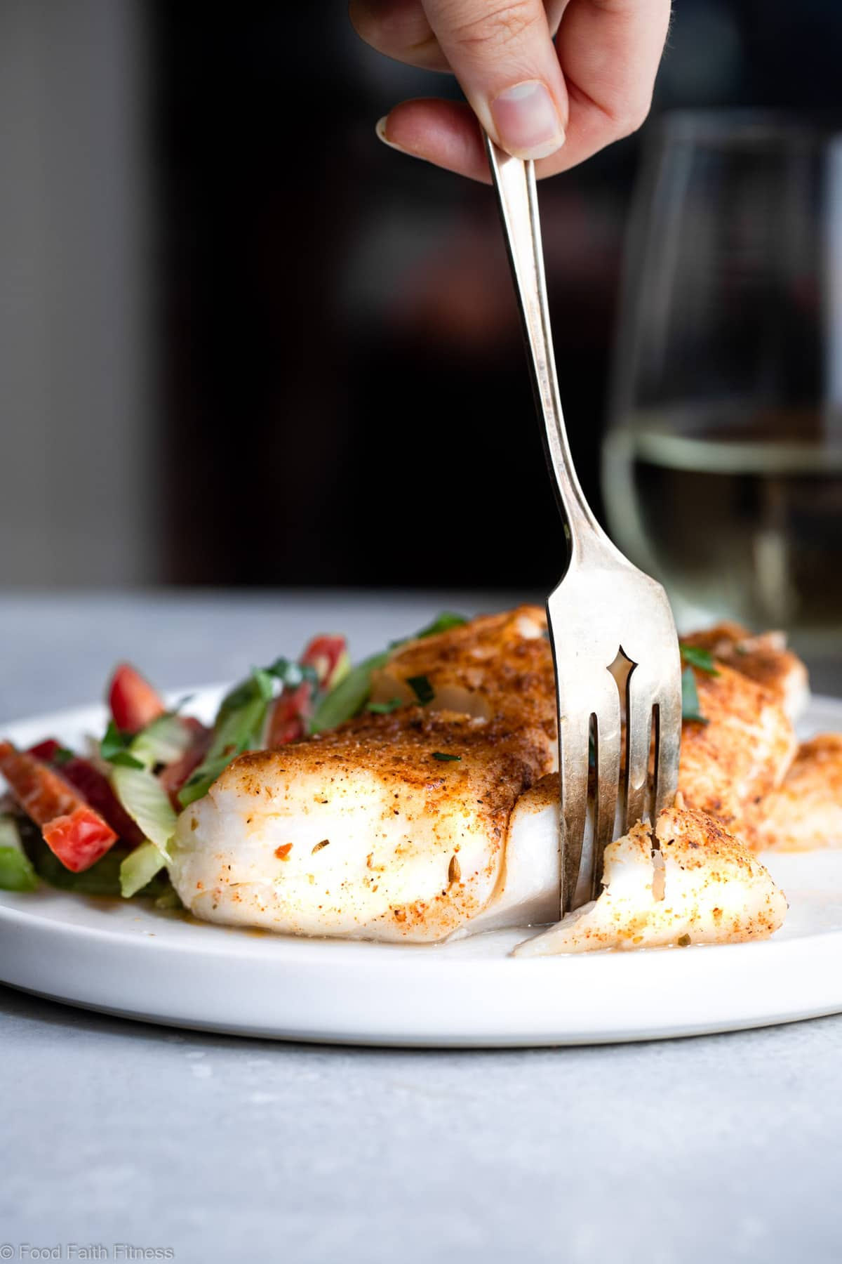 Cutting Cajun Grilled Cod on a plate