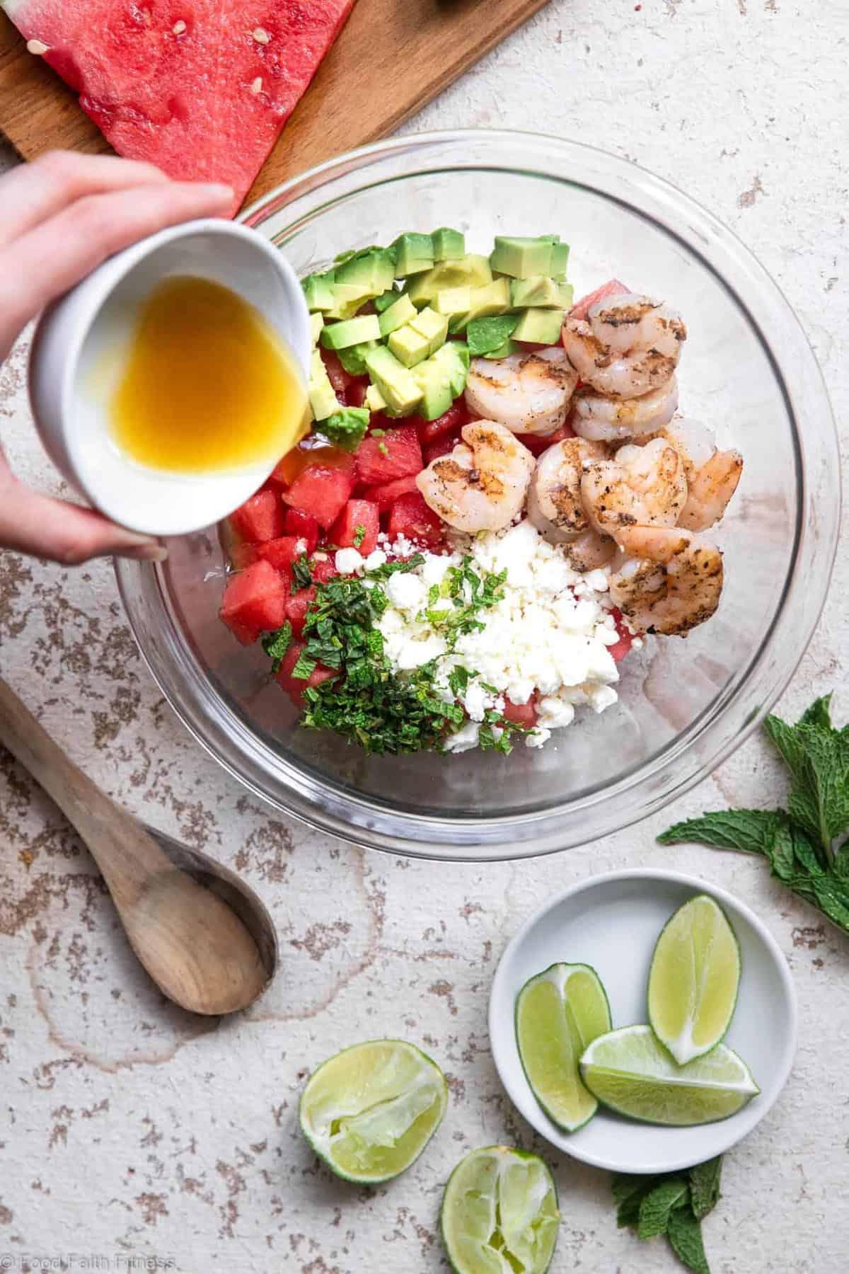 Pouring dressing onto a shrimp avocado salad with watermelon