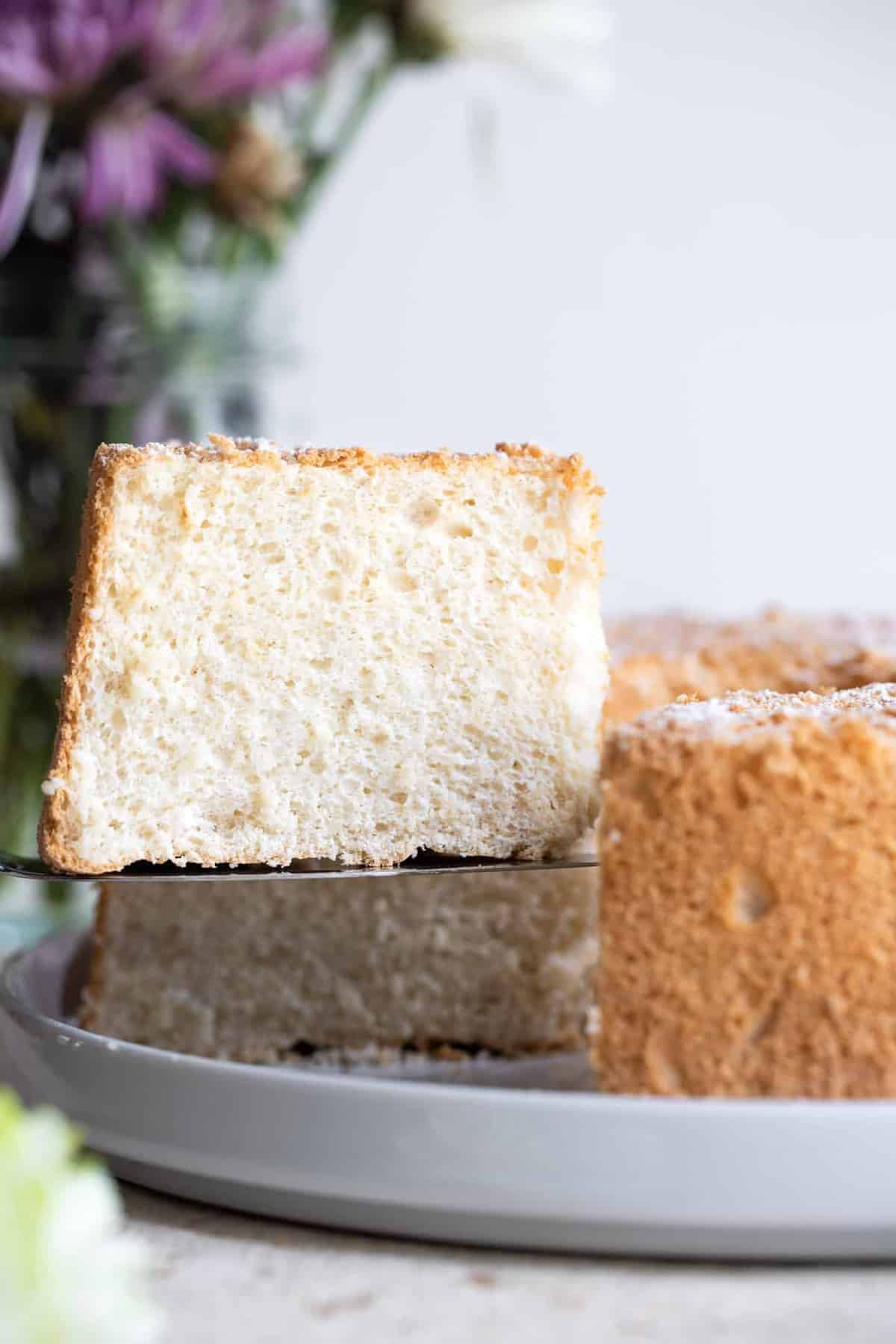 Sugar free angel food cake slice lifting out of a cake