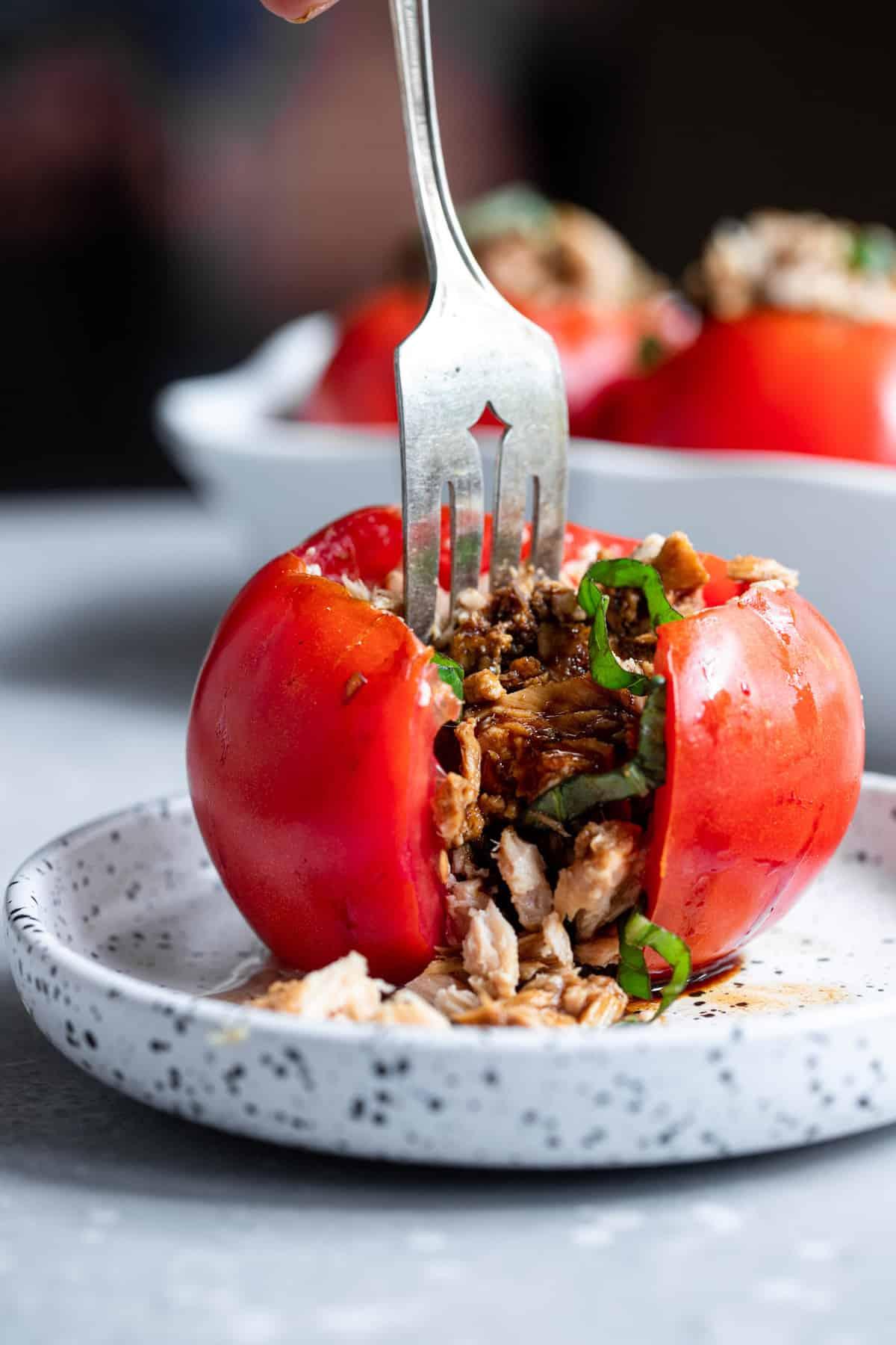 a fork cutting into tuna stuffed tomatoes