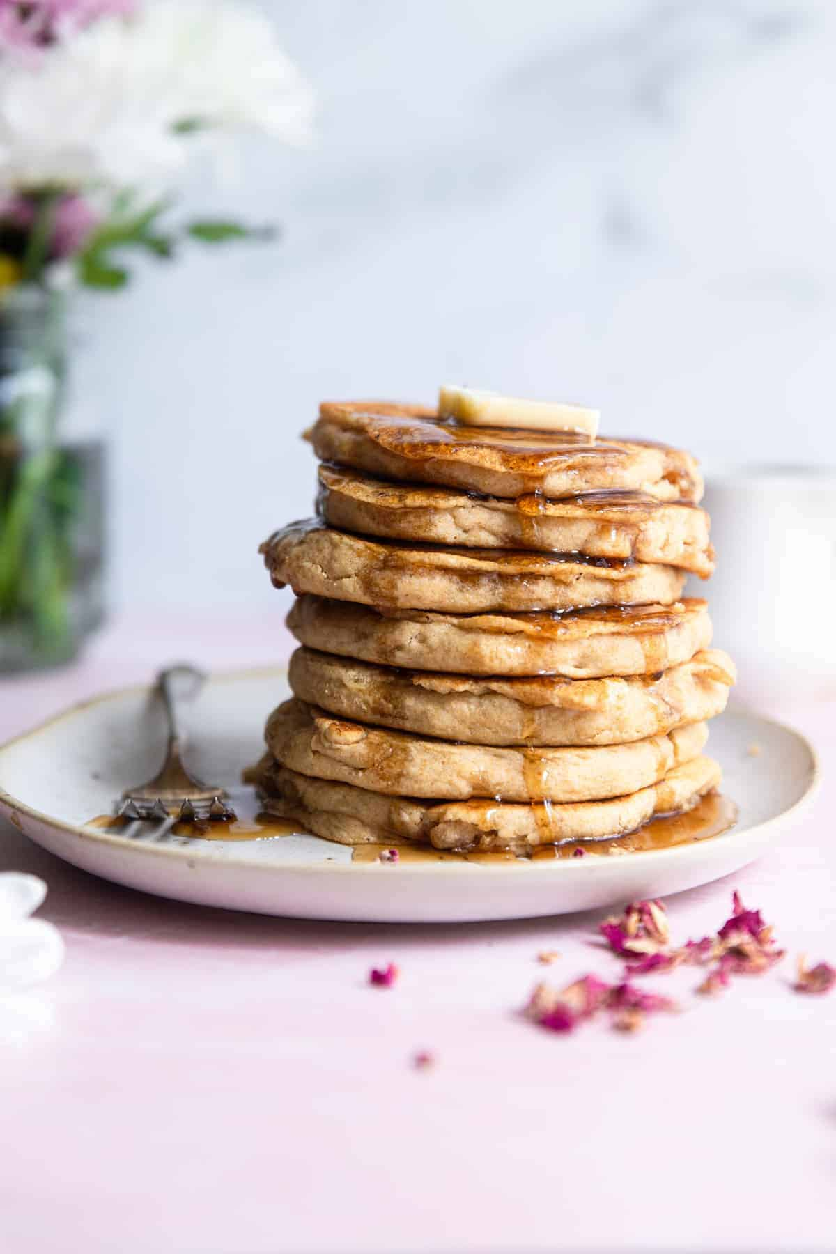 a stack of whole wheat vegan pancakes with butter and syrup