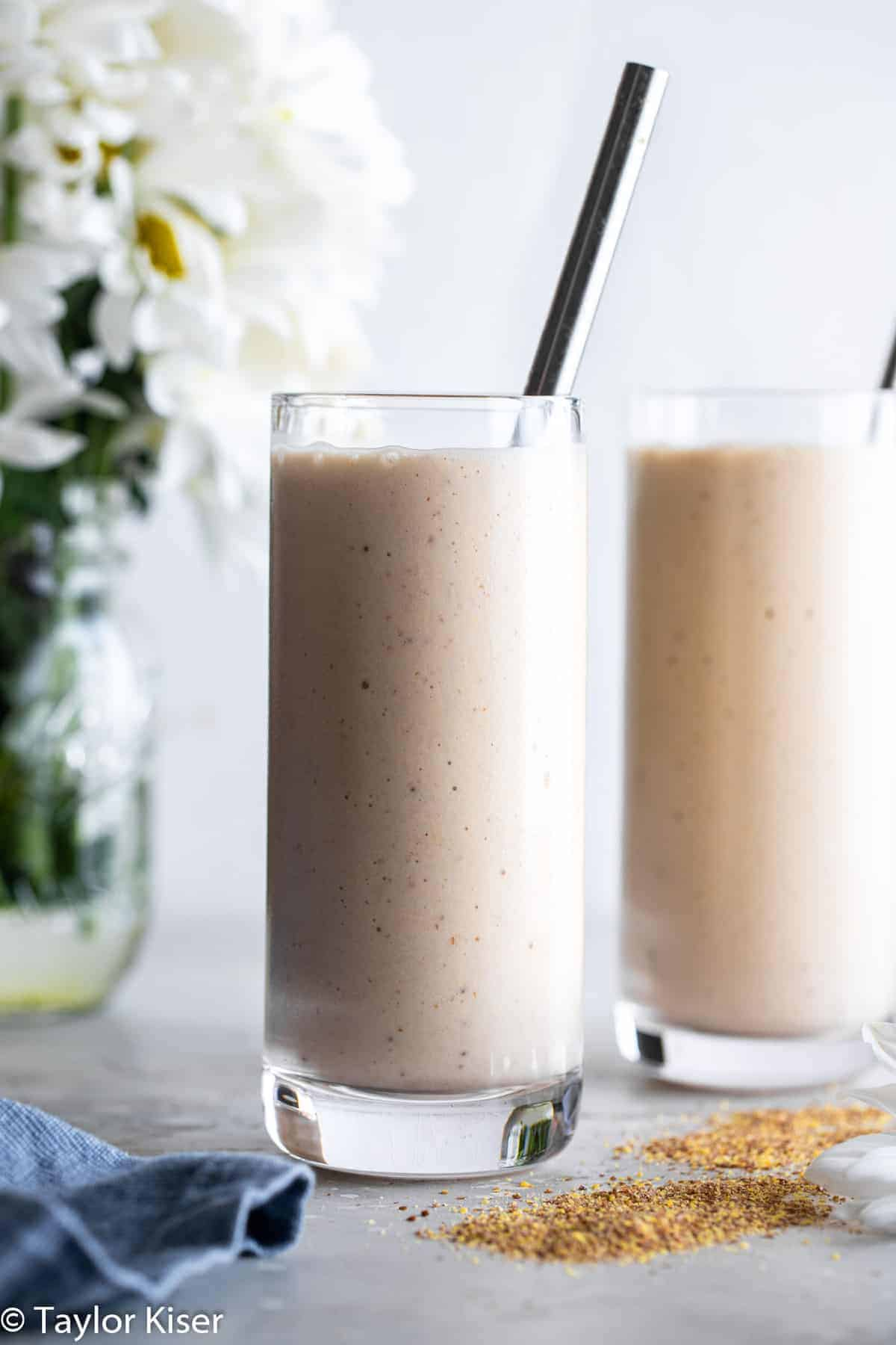 two flax seed smoothies on a table with flowers