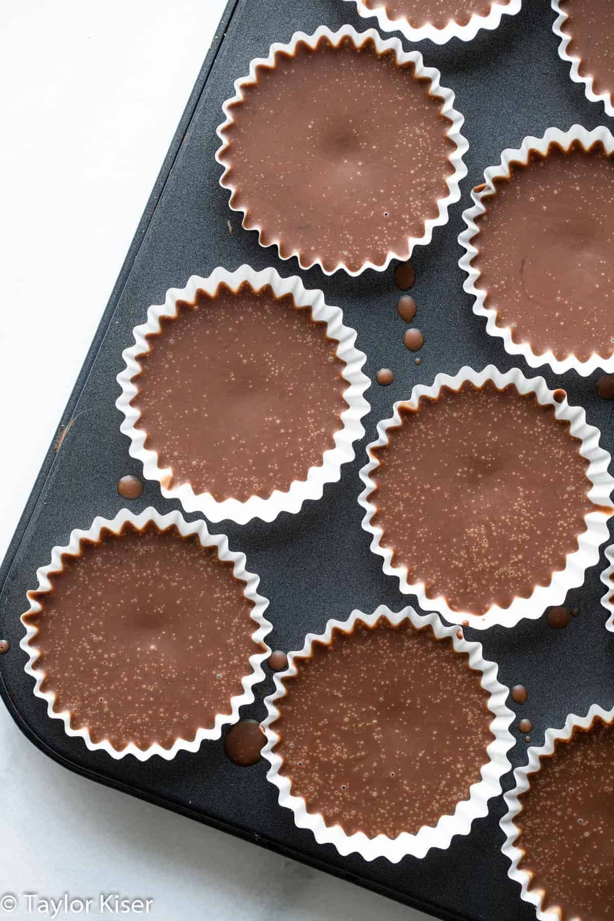 chocolate peanut butter keto fat bombs in a muffin tin