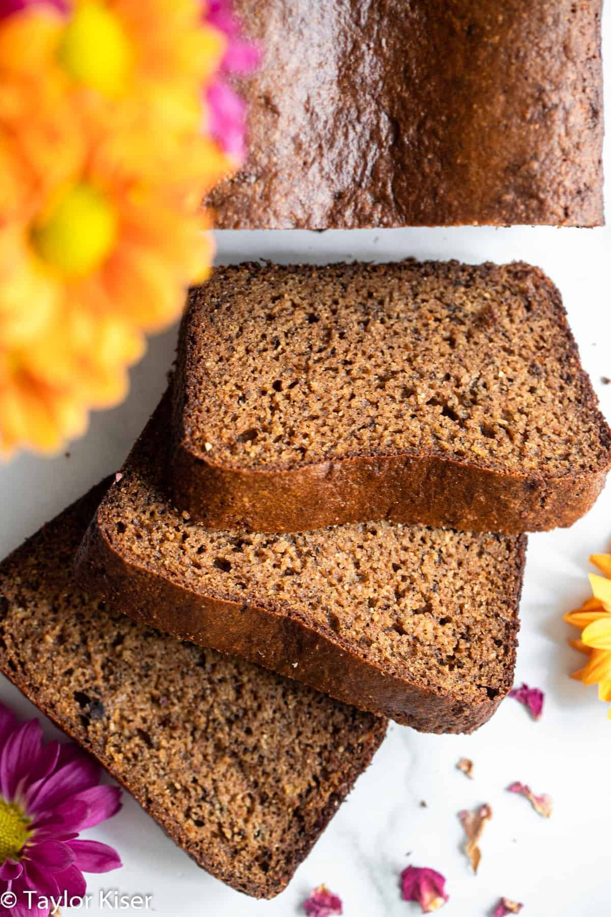 Slices of protein banana bread with flowers on a table