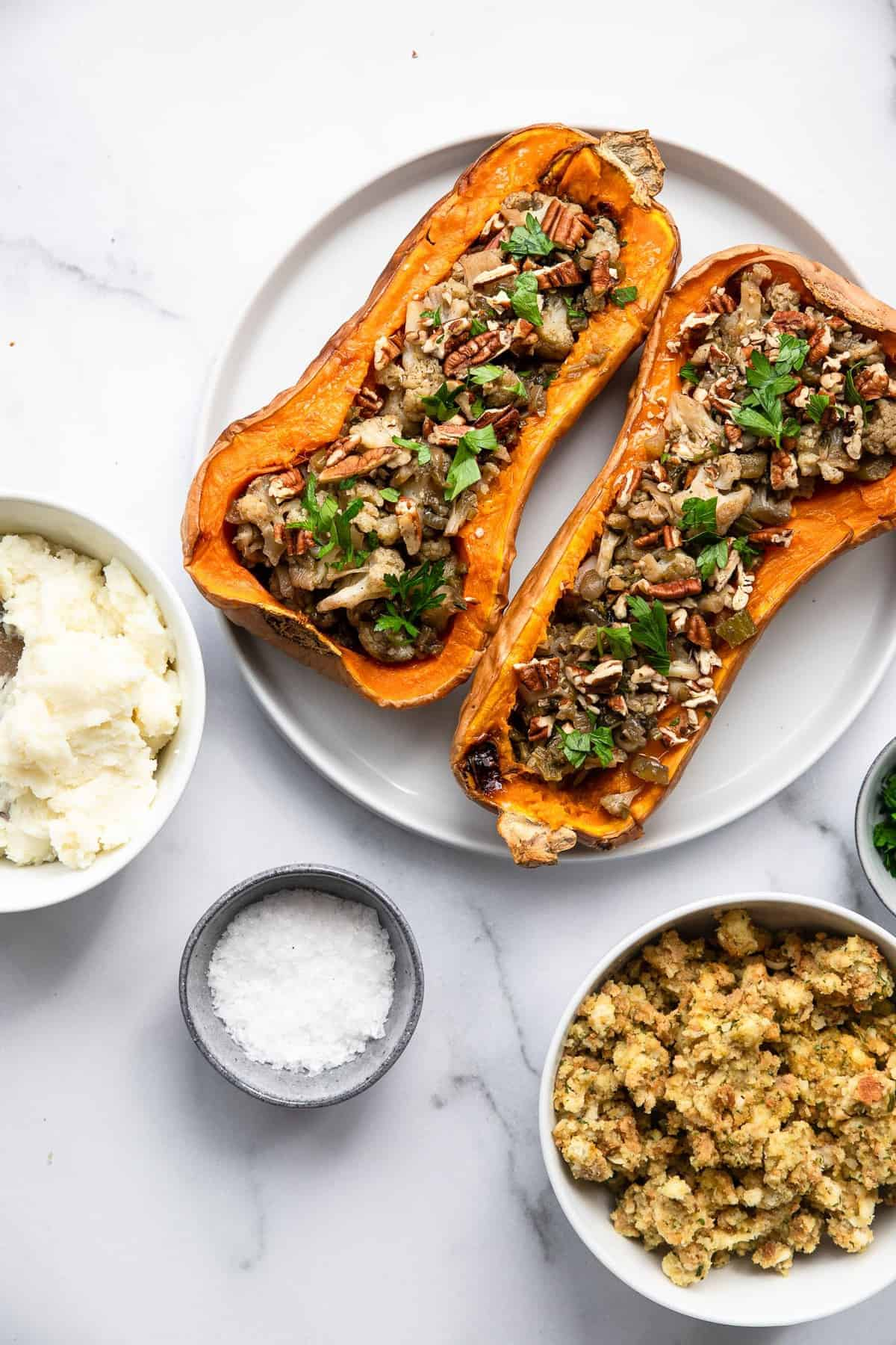vegan butternut squash on a plate with a bowl of mashed potatoes on the side
