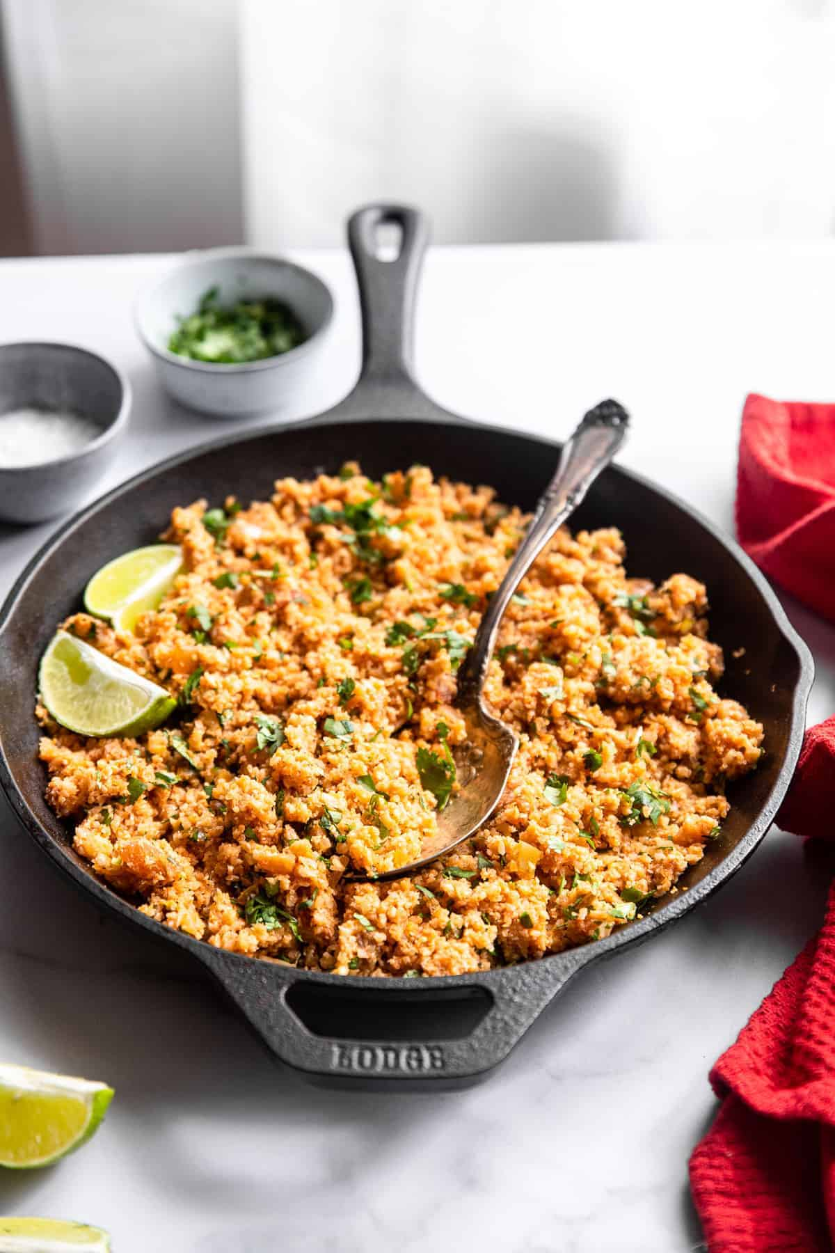 keto mexican cauliflower rice on a table with cilantro and limes