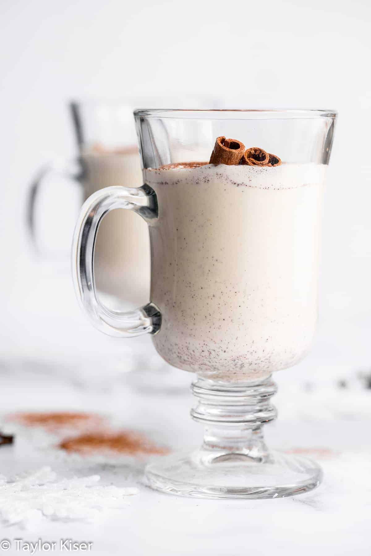 A glass of sugar free eggnog with cinnamon sticks in it