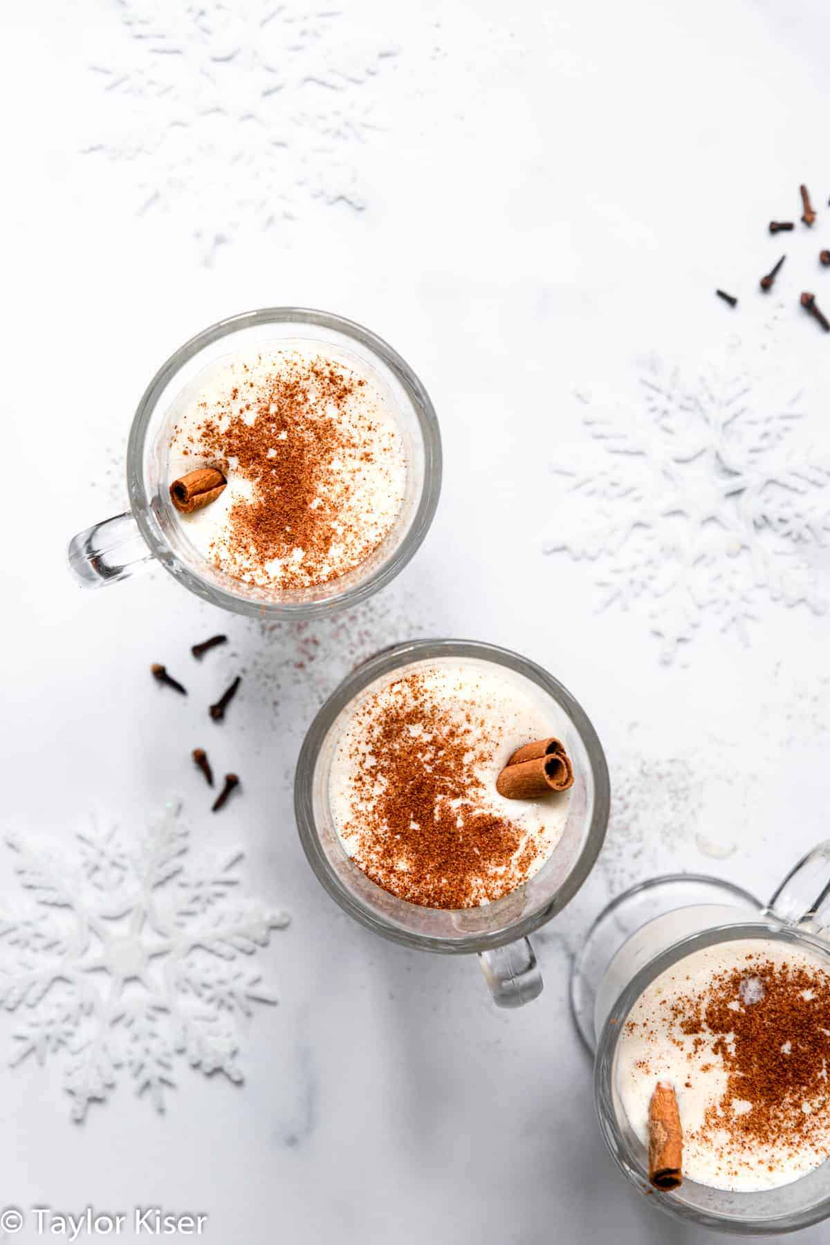 3 glasses of low carb eggnog with cinnamon sticks and nutmeg on top