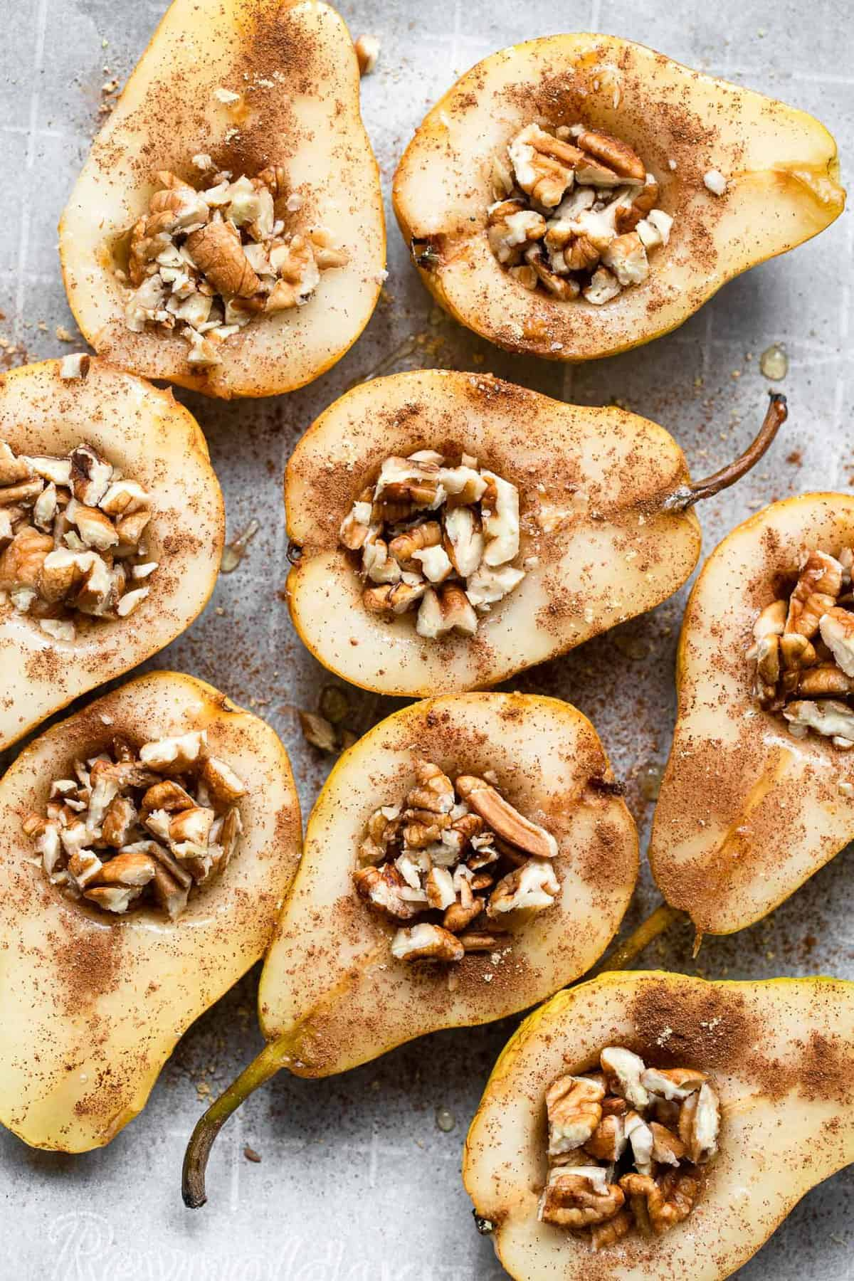 whole baked pears on a baking sheet