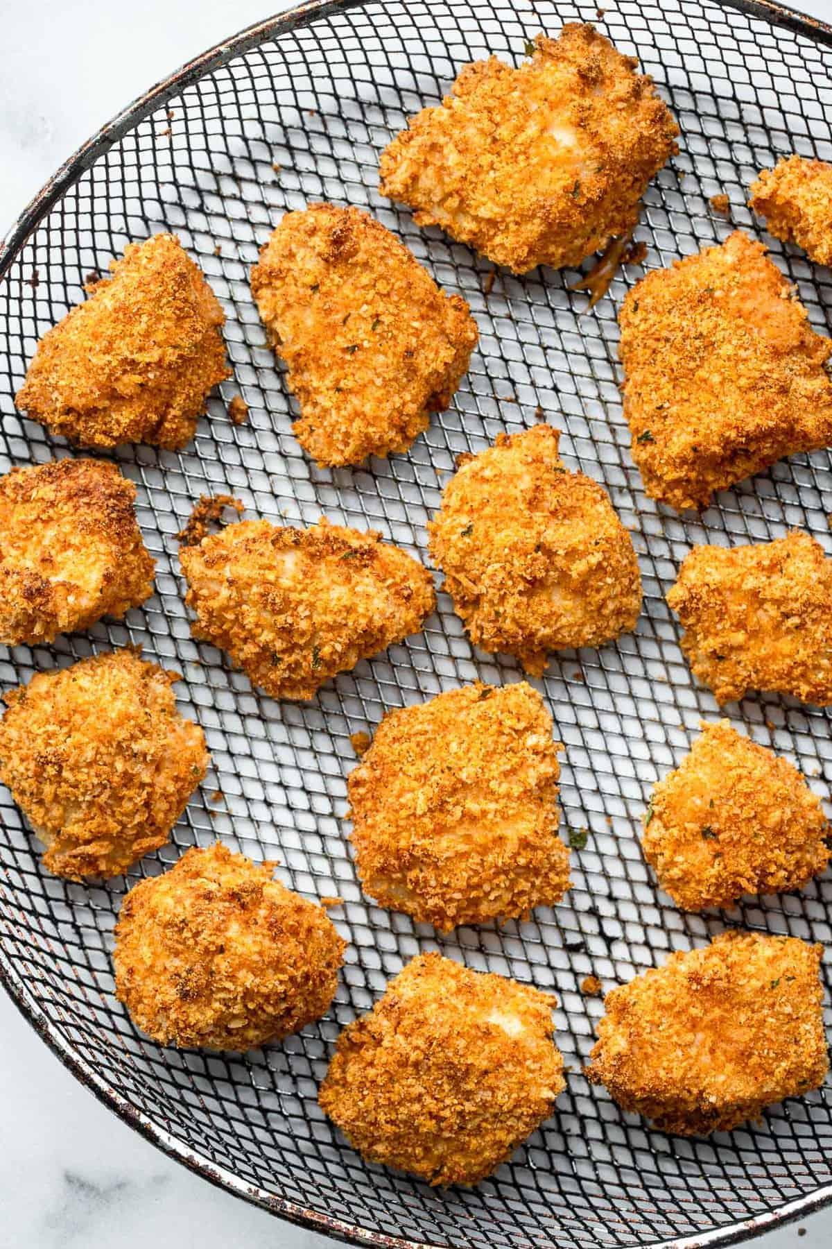 chicken nuggets in air fryer on a mesh basket