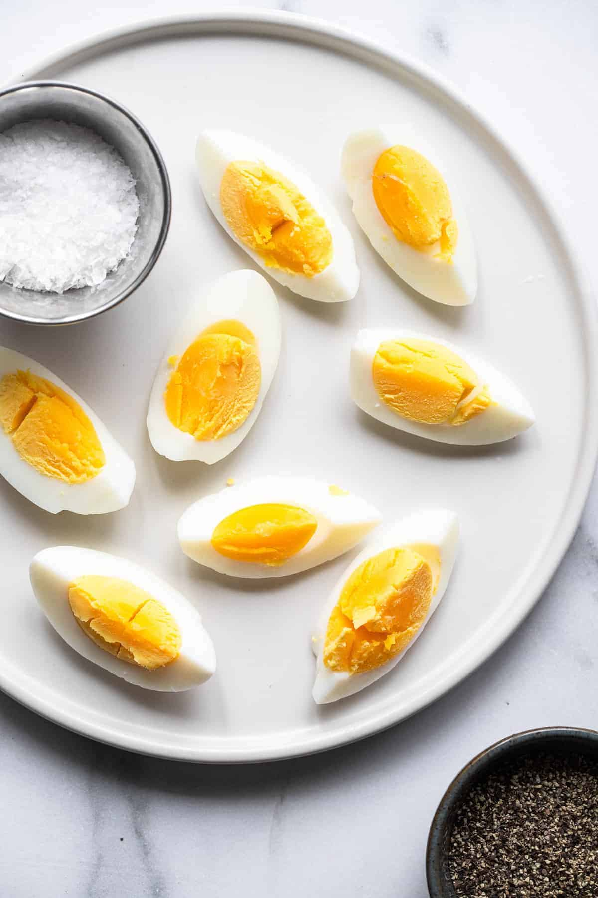 sliced air fryer hard boiled eggs on a plate with a bowl of salt