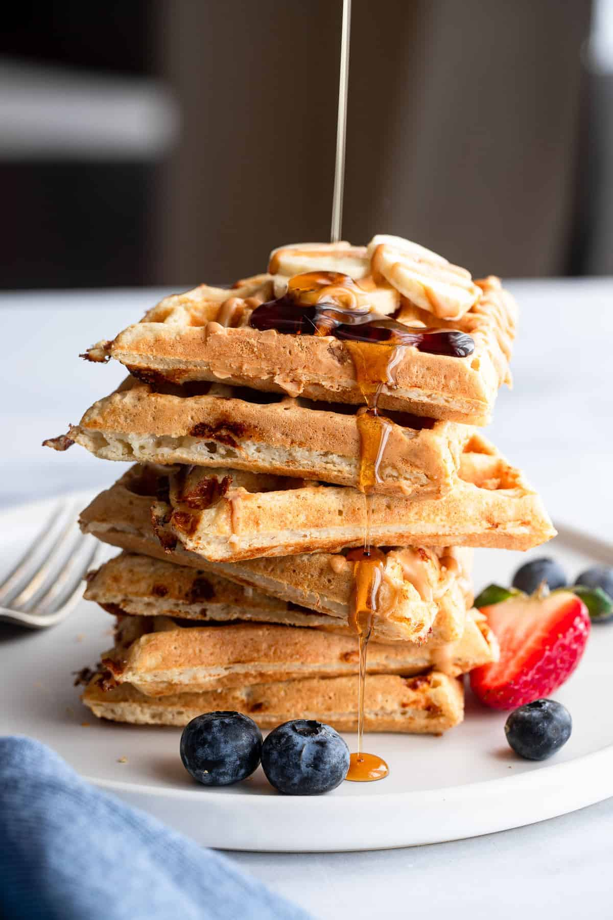 a stack of protein waffles drizzled with maple syrup