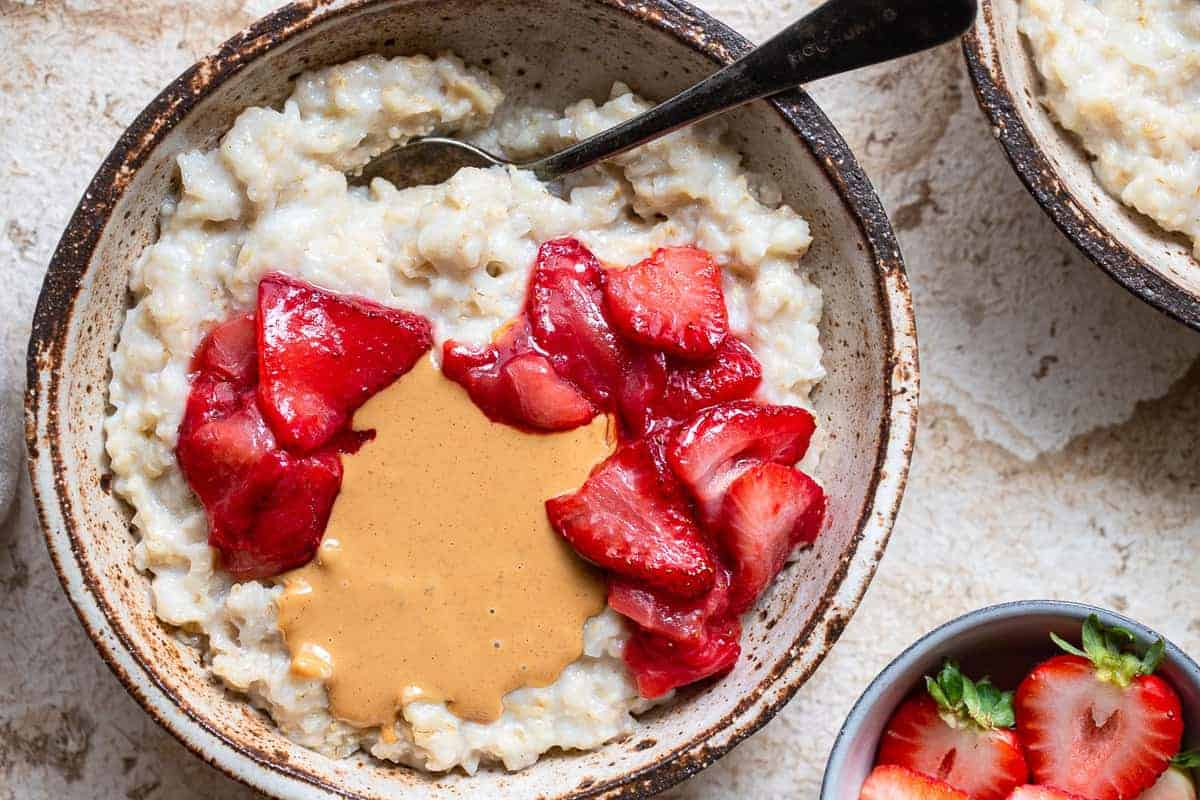 cauliflower oats on bowl with strawberries and peanut butter