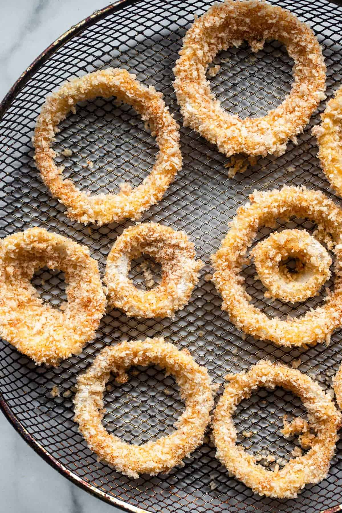 Onion rings air fryer on a mesh basket ready to be cooked