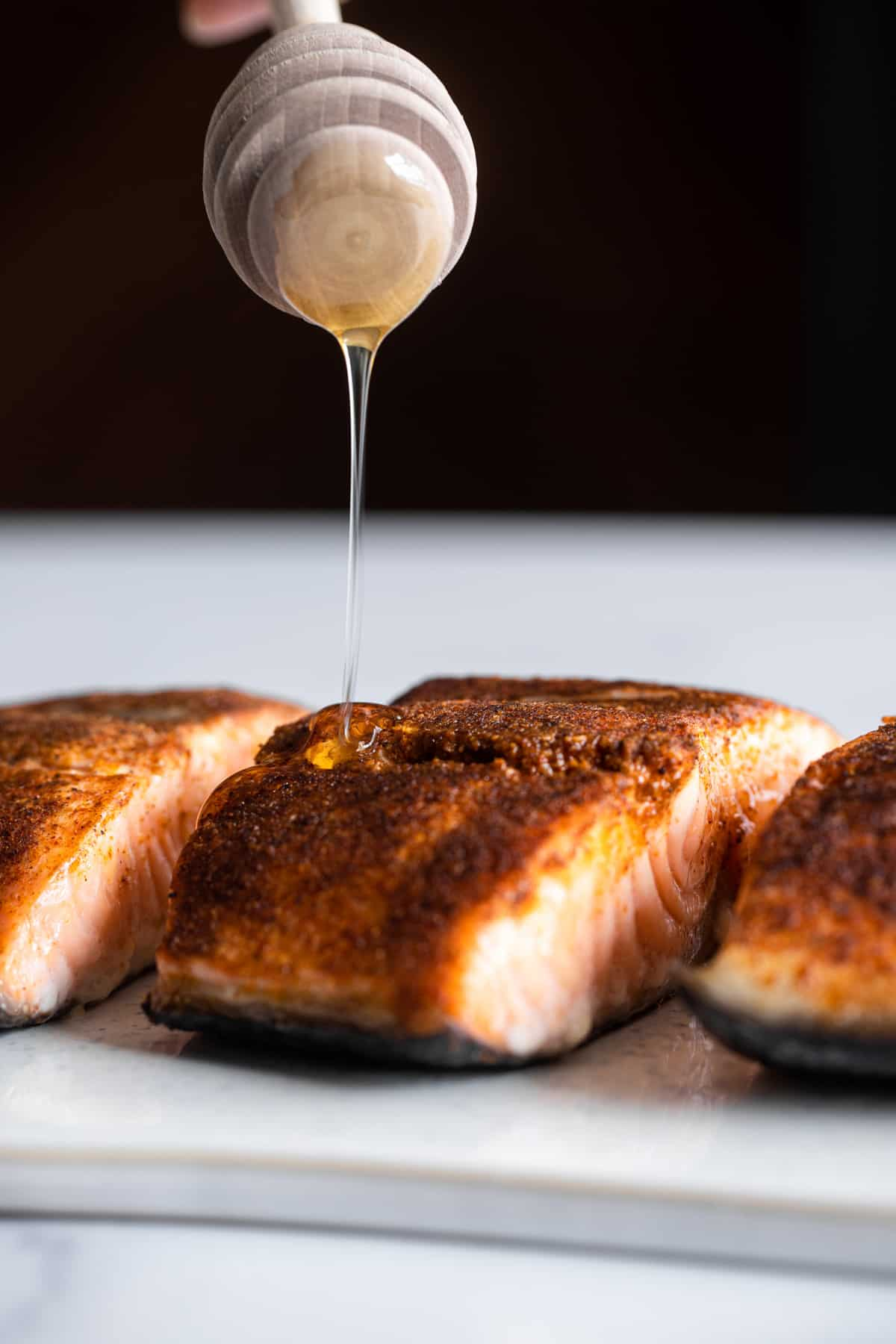 Honey Cajun Salmon on a plate being drizzled with honey