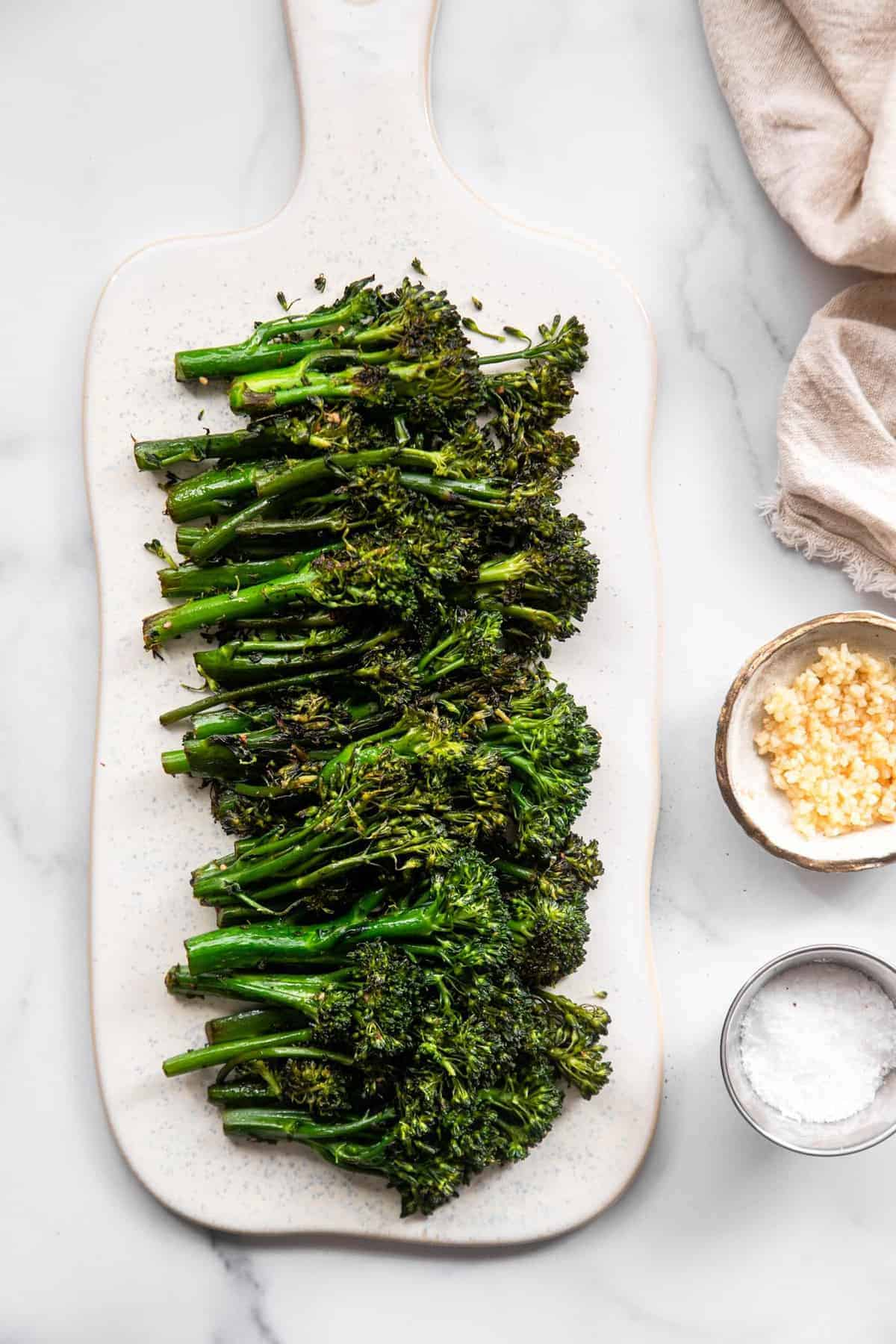 Sautéed broccolini on a plate with seasonings on the side
