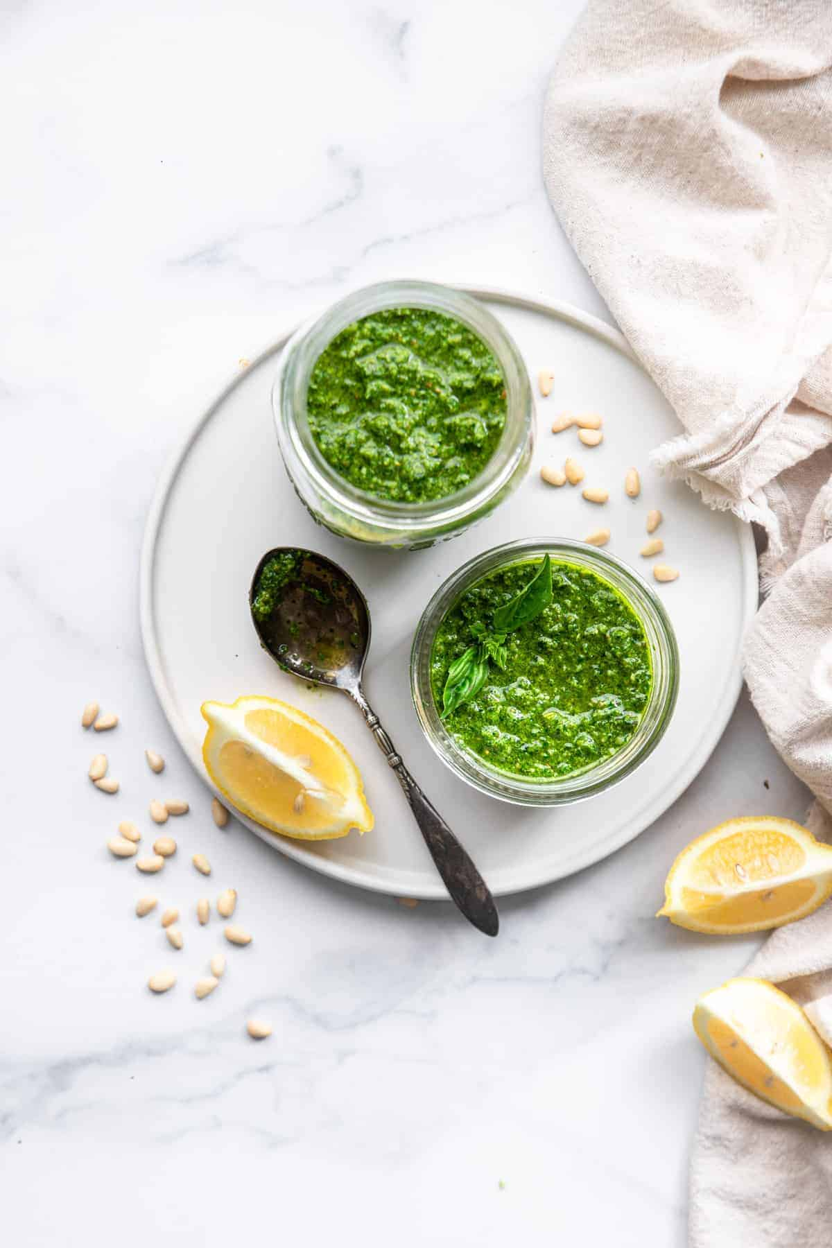 Spinach pesto sauce overview on a serving plate with lemon and a spoon