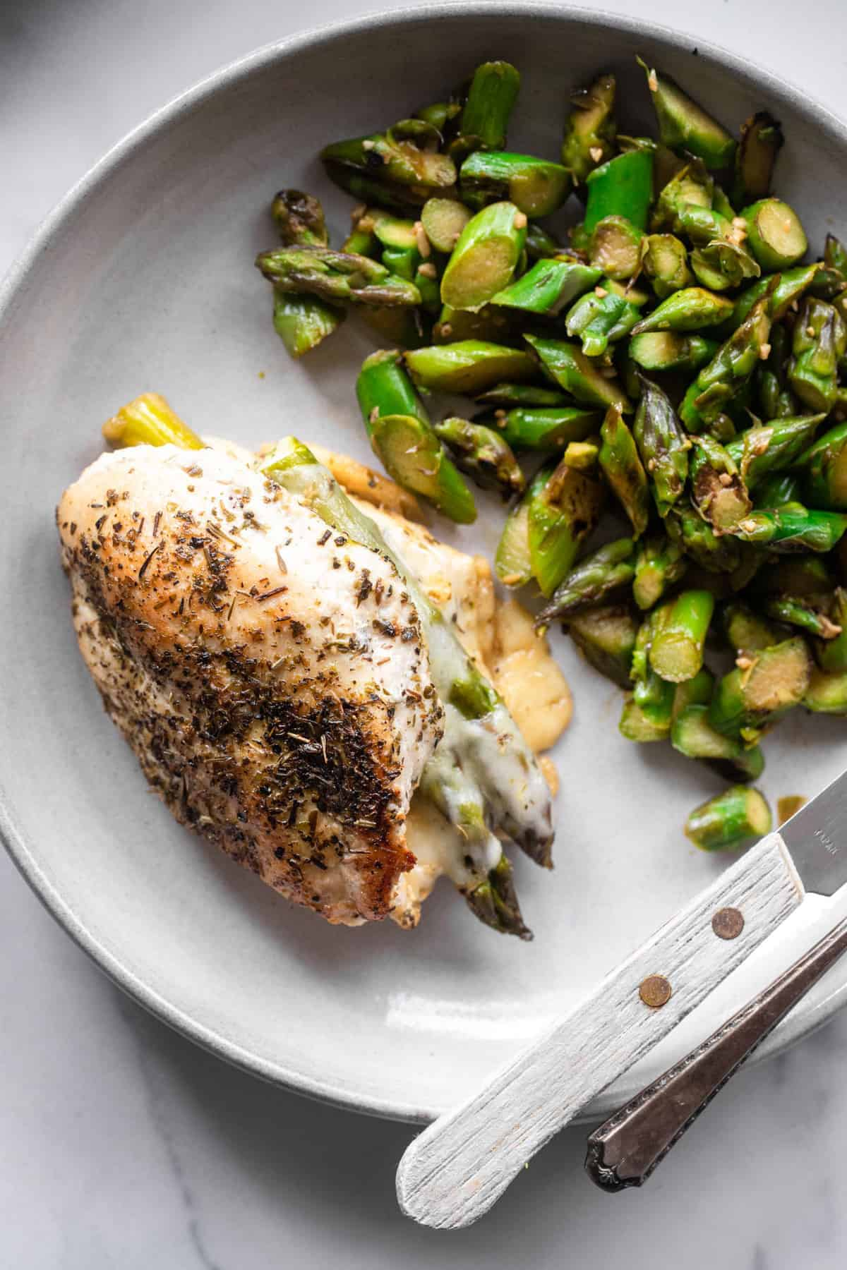 asparagus stuffed chicken on a plate with asparagus stir fry