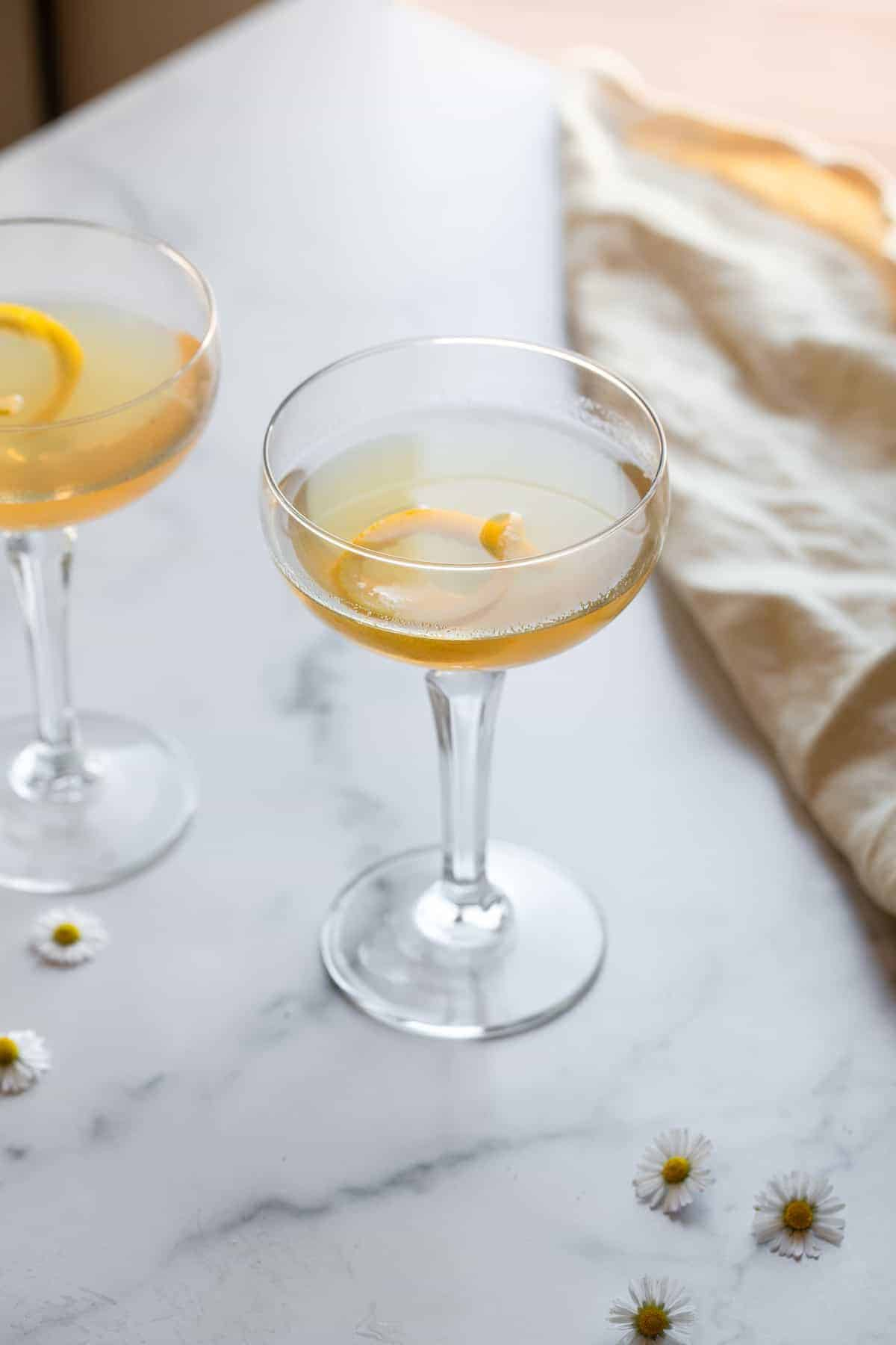 side view of bees knees cocktail with lemon peel in glass