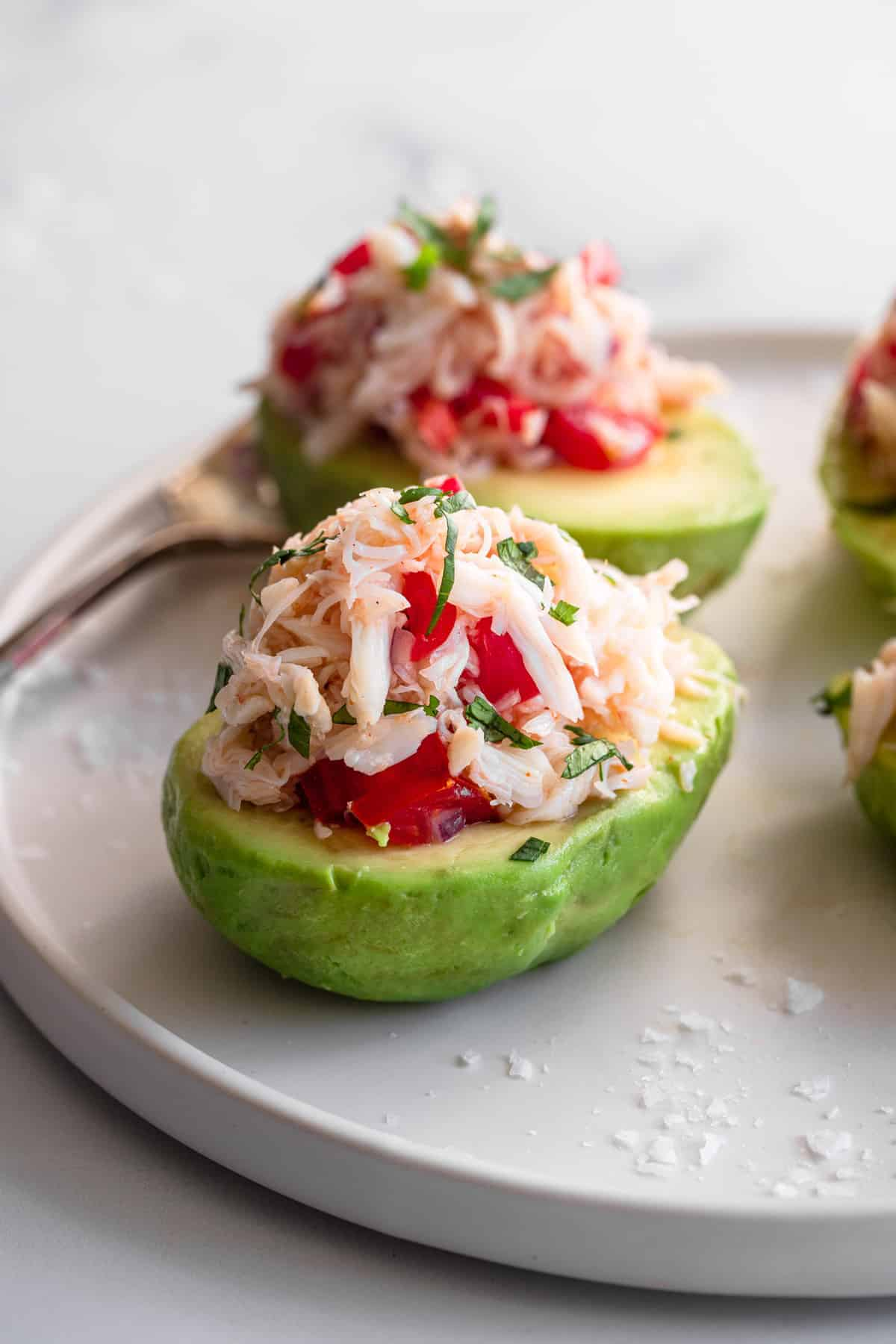close up top view of crab avocado salad on a plate with fork