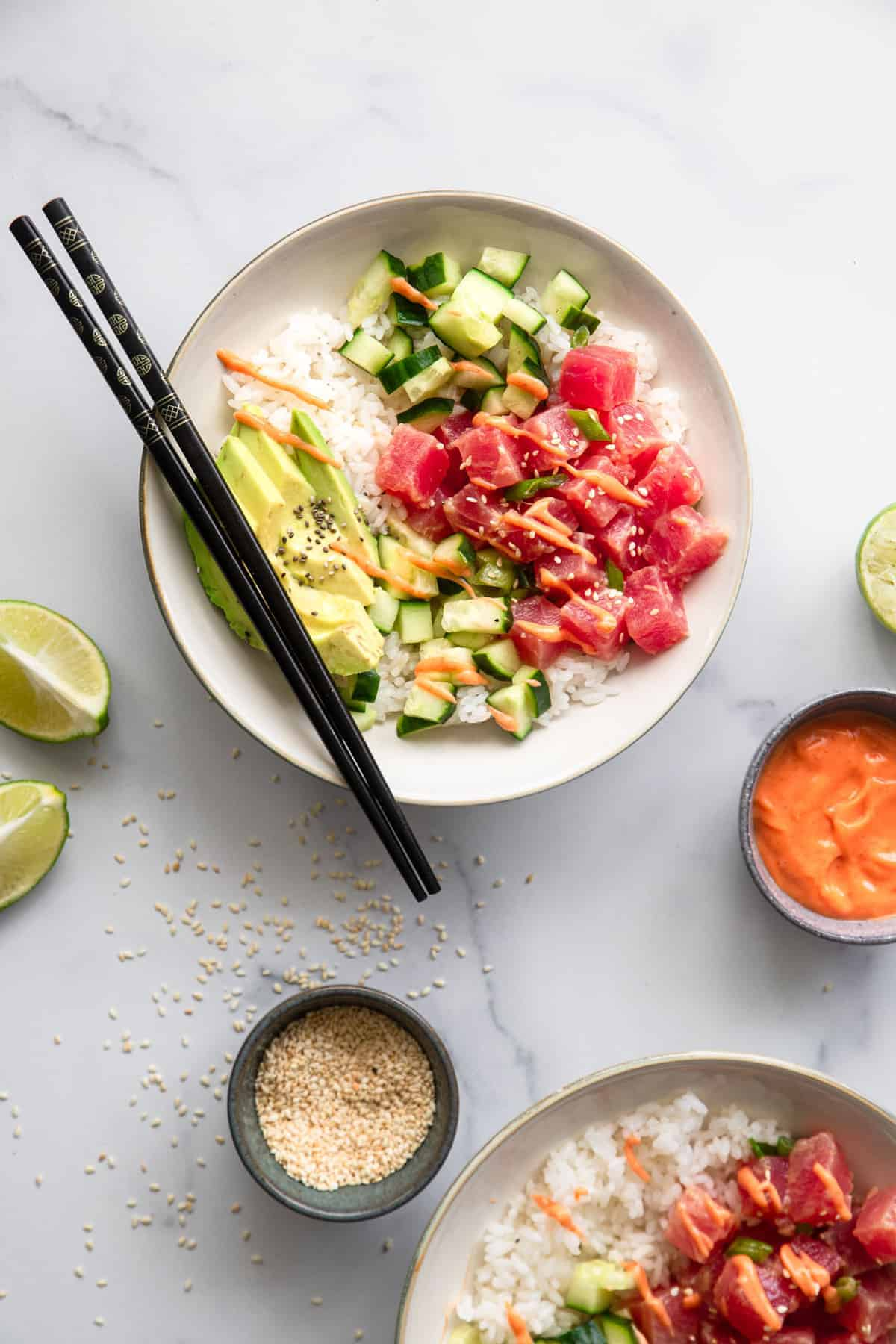 tuna poke bowl recipe on a bowl with chopsticks and sauces