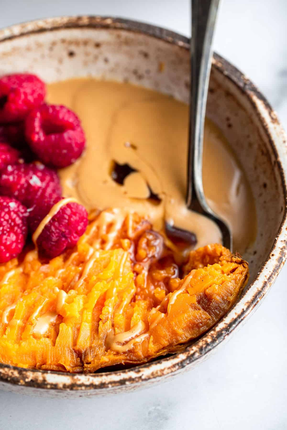 close up of sweet potato breakfast bowl with a spoon inside