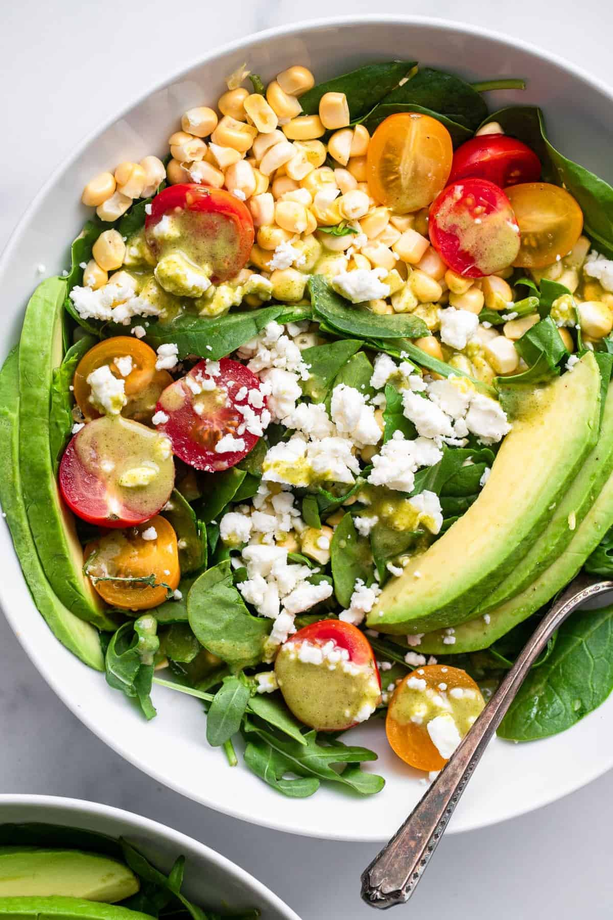 close up view of corn feta salad in a bowl with a spoon