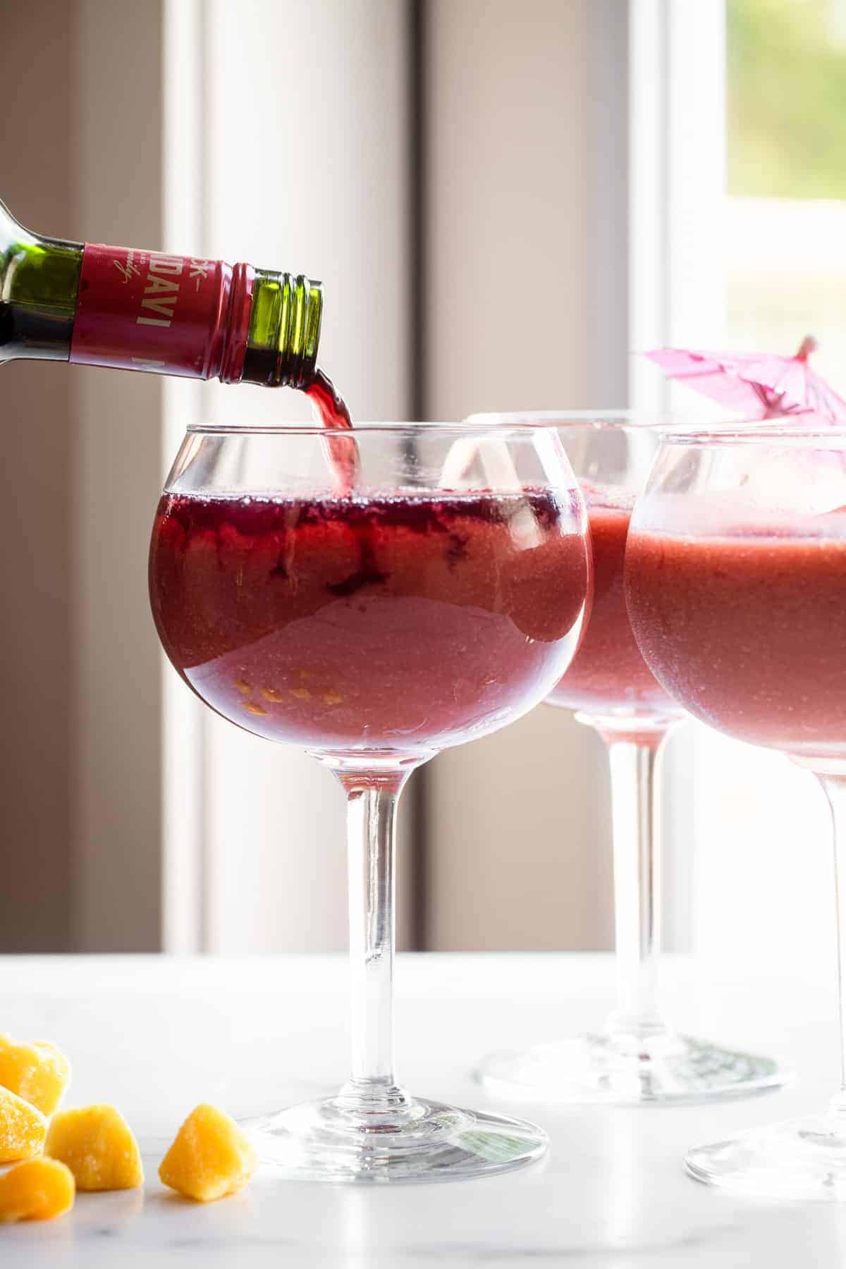frozen sangria recipe in a glass with wine being poured in