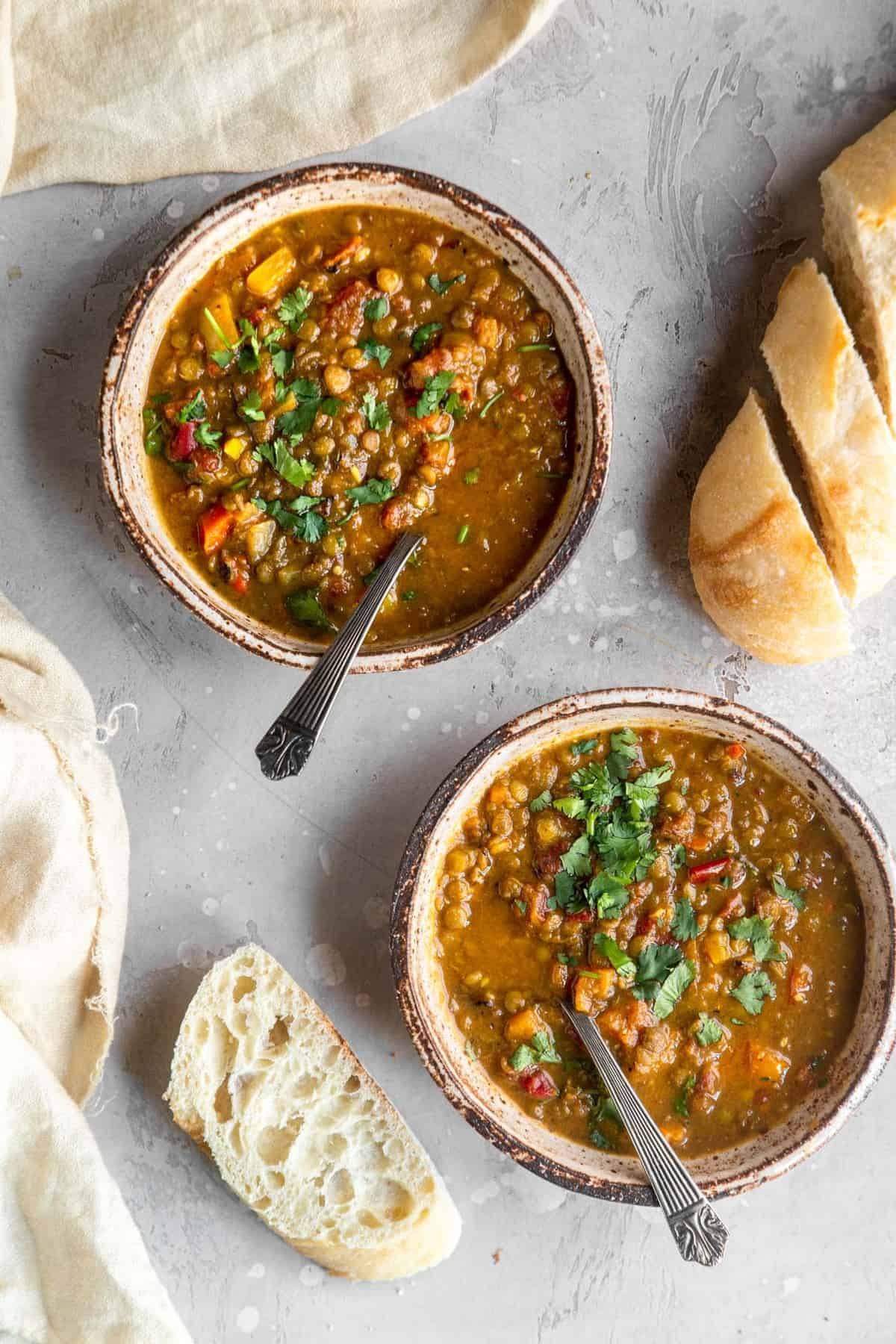 two bowls of curry lentil soup in bowls on a table with bread