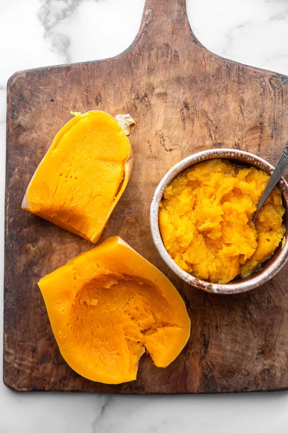 Instant Pot Butternut Squash on a cutting board with inside scooped out