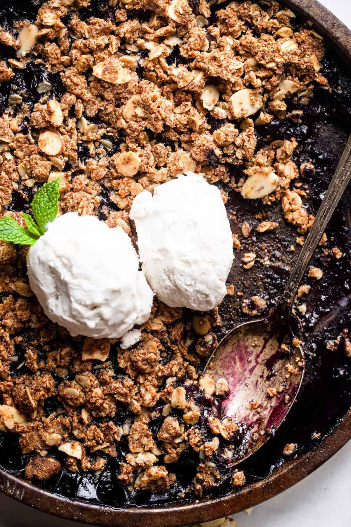 Gluten Free Blueberry Crisp with ice cream on top and a spoon