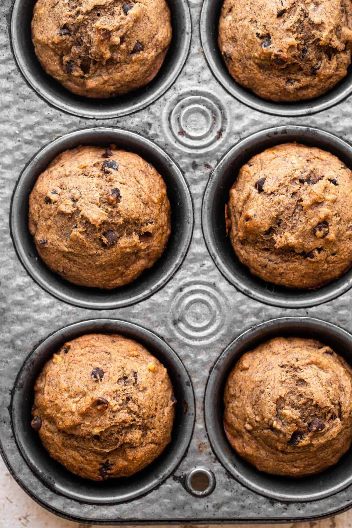 extreme close up of whole wheat banana muffins in a muffin tin