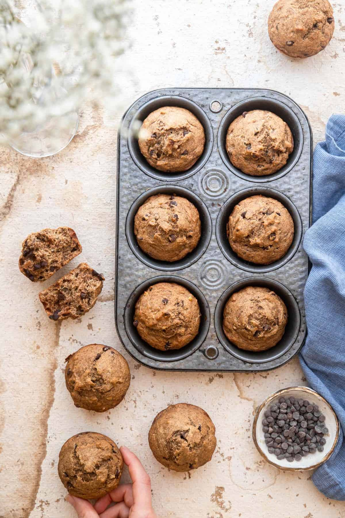 whole wheat banana muffins on a table in a muffin pan