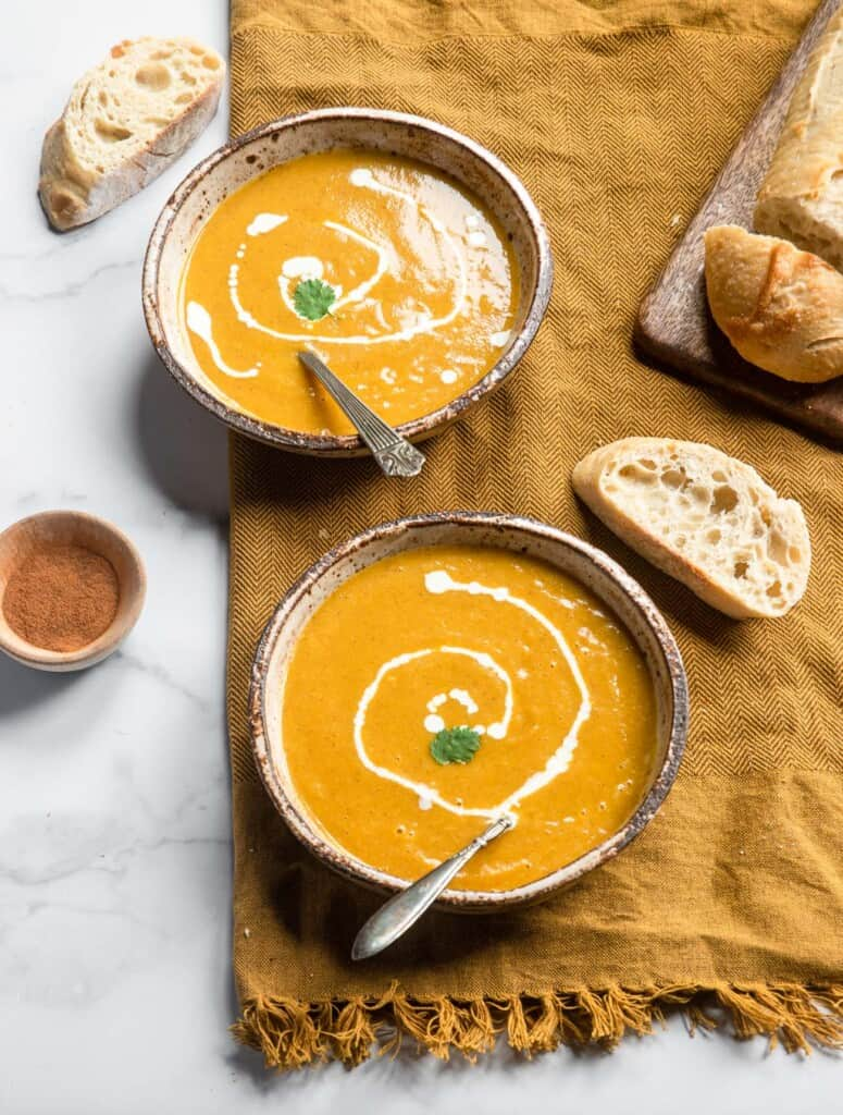 two bowls of Instant Pot Butternut Squash Soup with bread and seasoning on the side