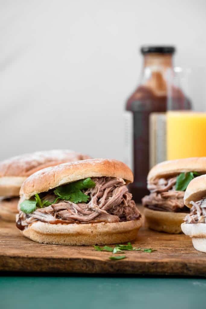 side view of Paleo pulled pork sandwich on a cutting board with BBQ sauce in the background