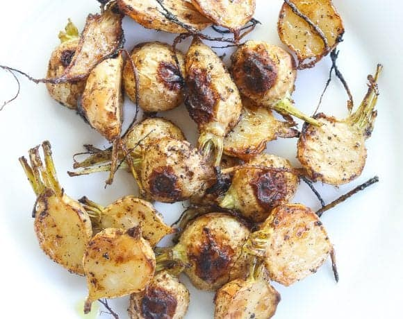 roasted turnips halved and on a white plate.