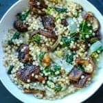 Creamy Israeli couscous with mushrooms and kale in a bowl