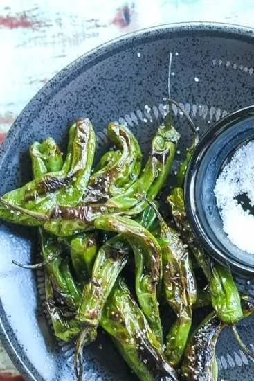 pan-fried shishito peppers on a black plate