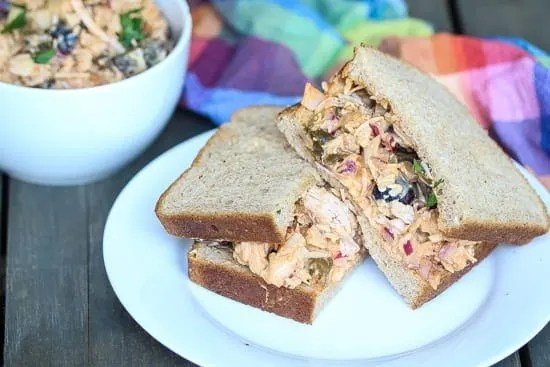 chicken salad sandwich halves on a plate with bowl of chicken salad in the background