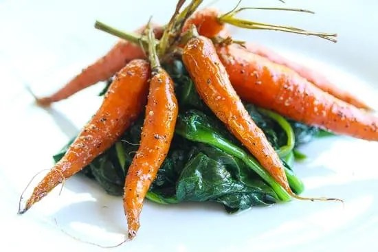 simple smoked carrots on a plate of spinach