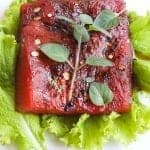 roasted watermelon steak on a plate with greens