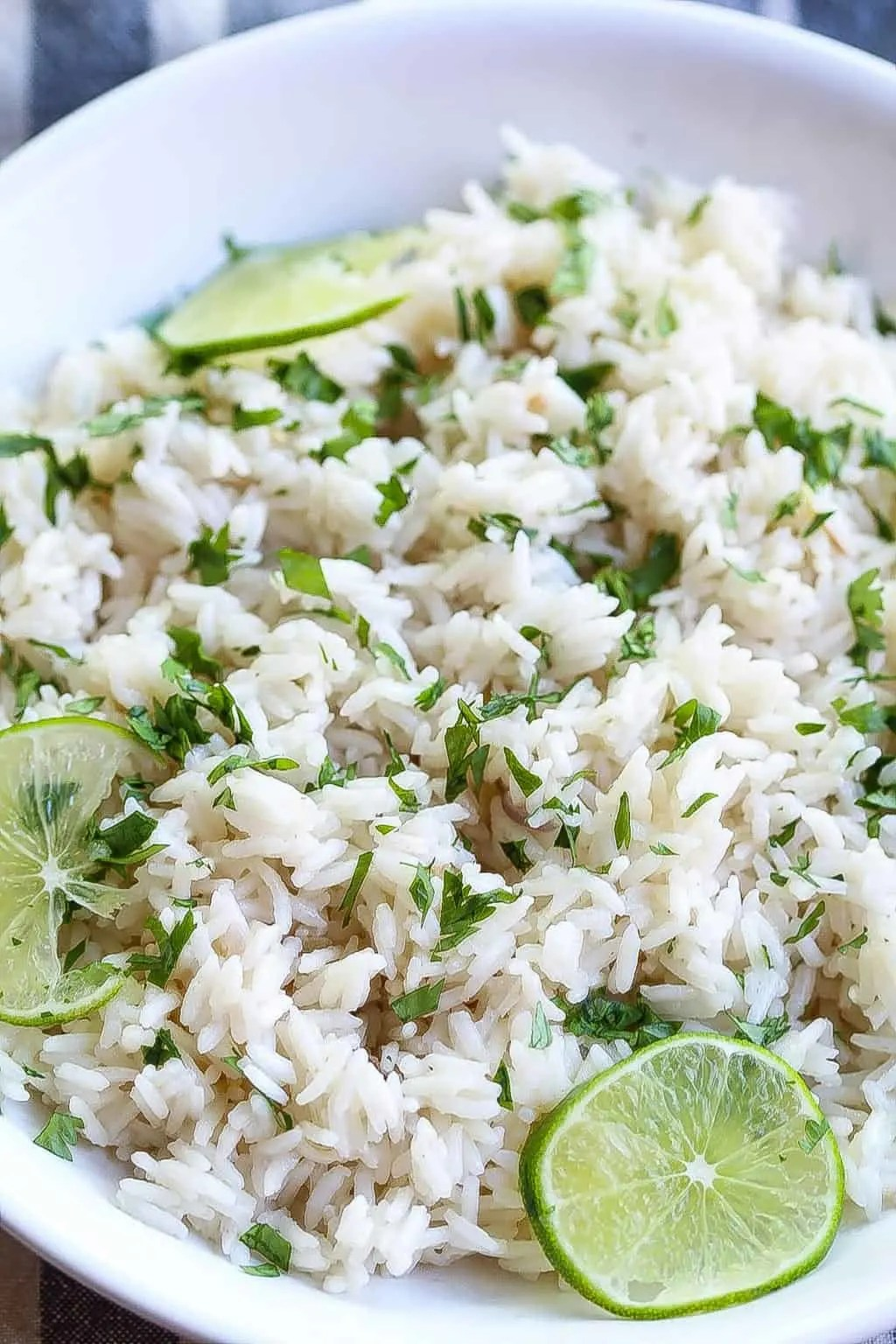 coconut ginger rice in a bowl and topped with limes and cilantro