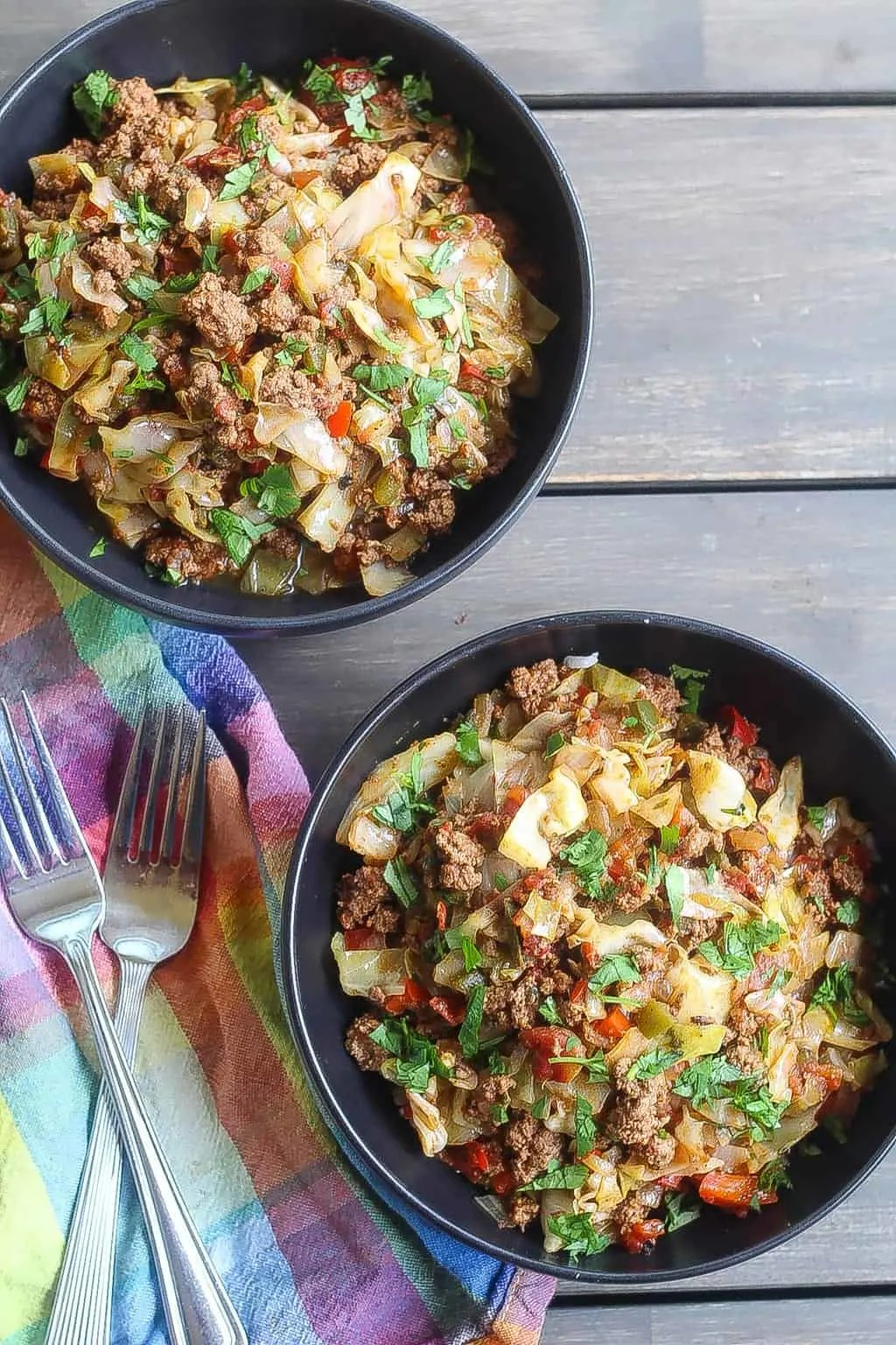 beef and cabbage stir fry in a black bowl