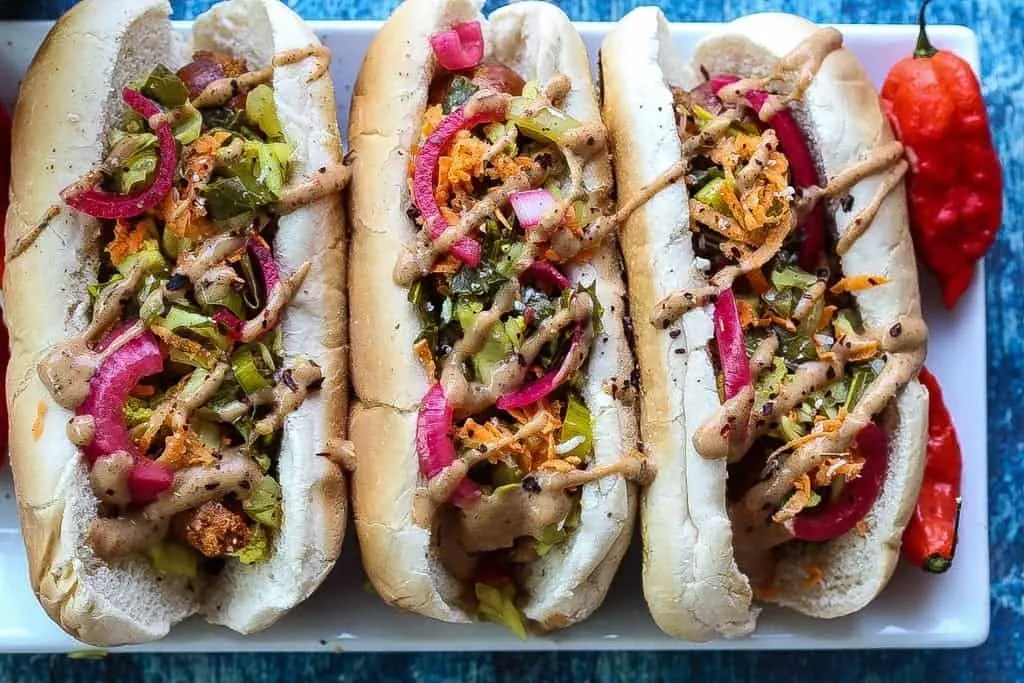 andouille sausage hot dog topped with mustard, pickled red onions, and chow chow